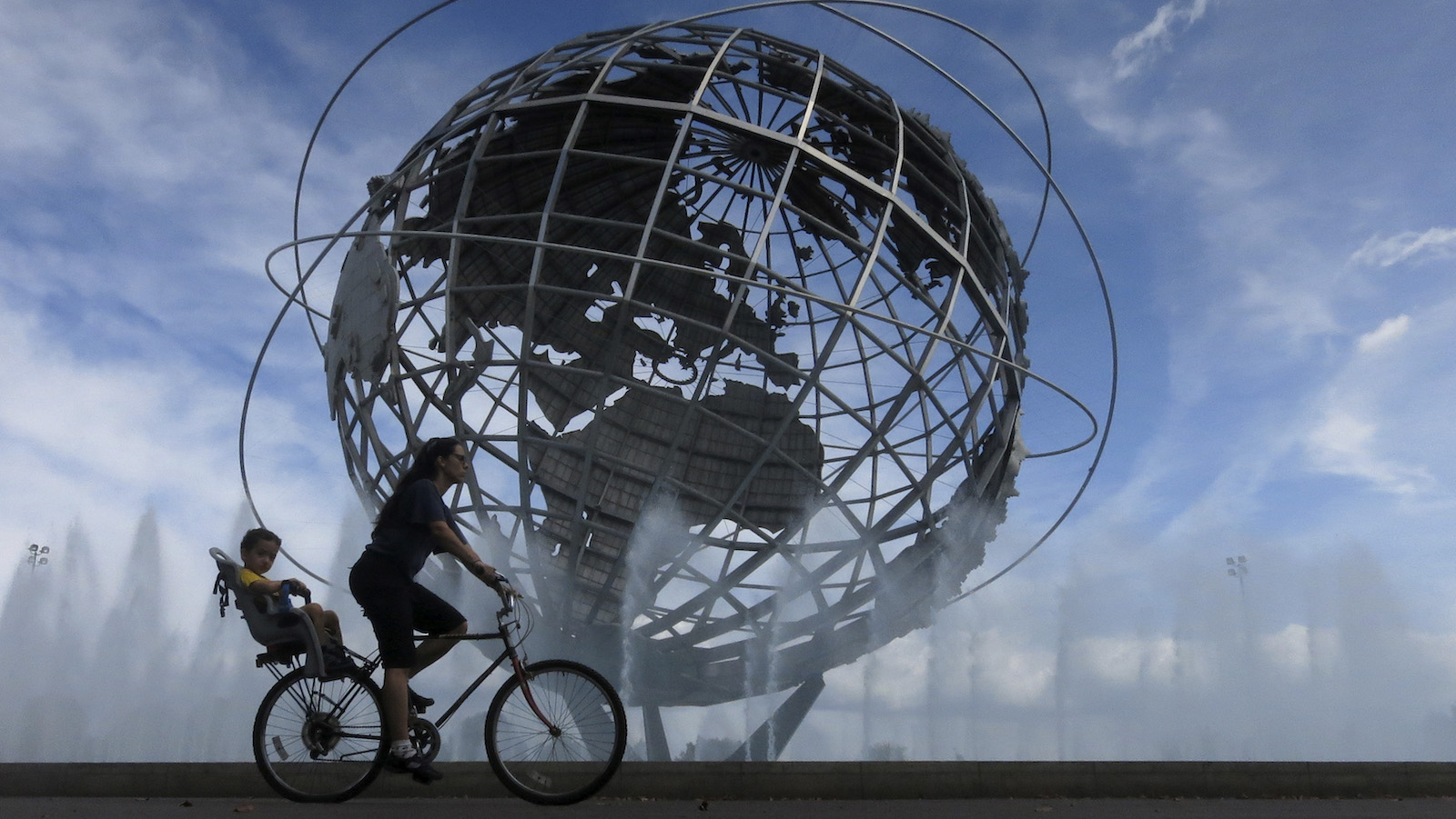A woman and her son ride past the Unisphere in Flushing Meadows Corona Park in Queens, New York September 5, 2013. New York City is iconic in any weather, but the warm season adds a special flavour to its bustling streets, leafy parks and world-famous skyline. The summer is about to draw to a close, as fall begins in the northern hemisphere with the Autumnal Equinox on September 22. Picture taken September 5, 2013. REUTERS/Gary Hershorn (UNITED STATES - Tags: CITYSCAPE SOCIETY TPX IMAGES OF THE DAY)   ATTENTION EDITORS: PICTURE 35 40 FOR PACKAGE  'NYC - A SEASON IN CITY'  SEARCH 'NYC HERSHORN' FOR ALL - RTX13T9Y