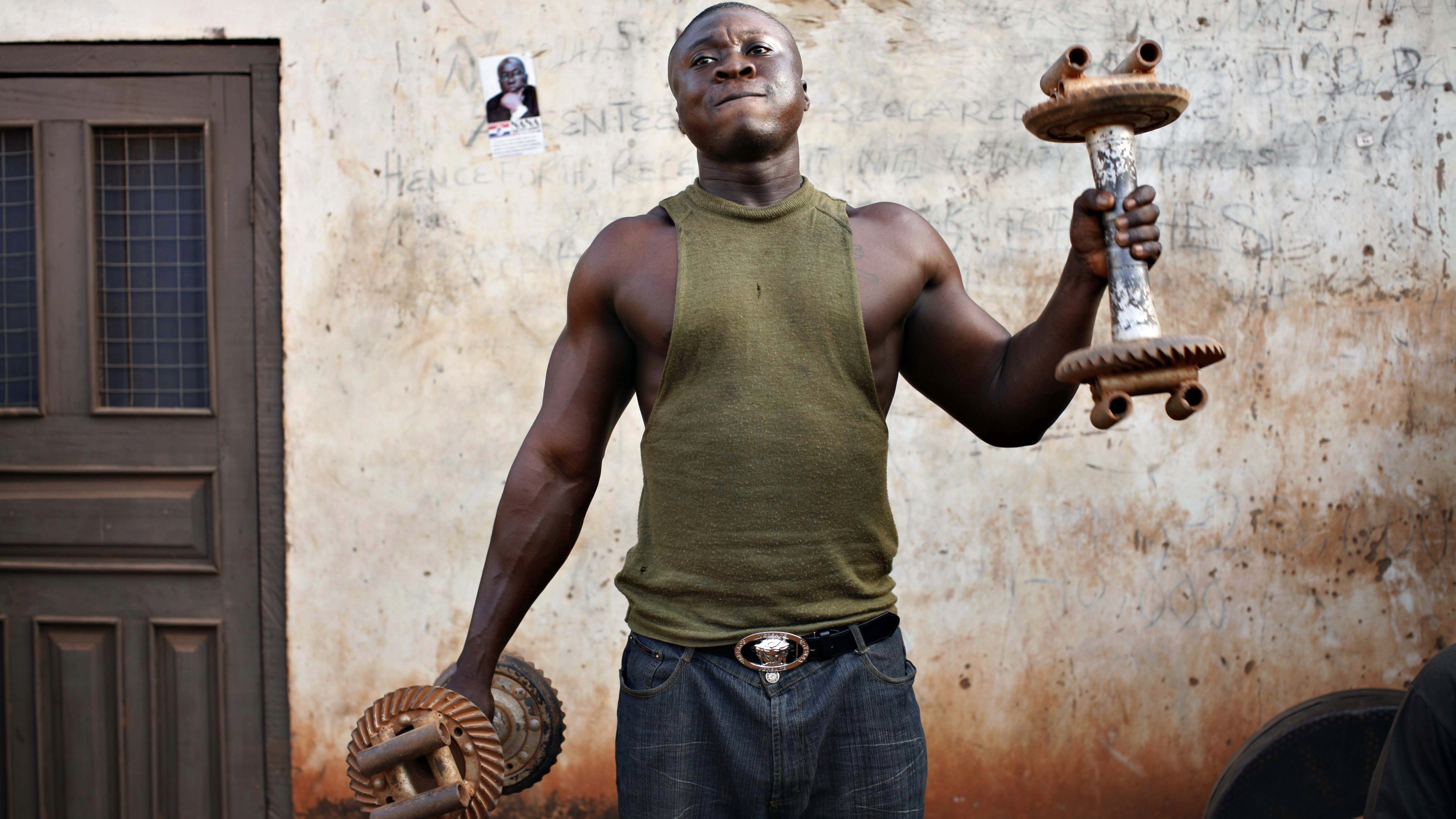 "A Ghanaian man nicknamed ""Tiger"" lifts weights at a makeshift outdoor gym in the northern city of Tamale, January 28, 2008.  REUTERS/Finbarr O'Reilly (GHANA) - RTR1WETR"