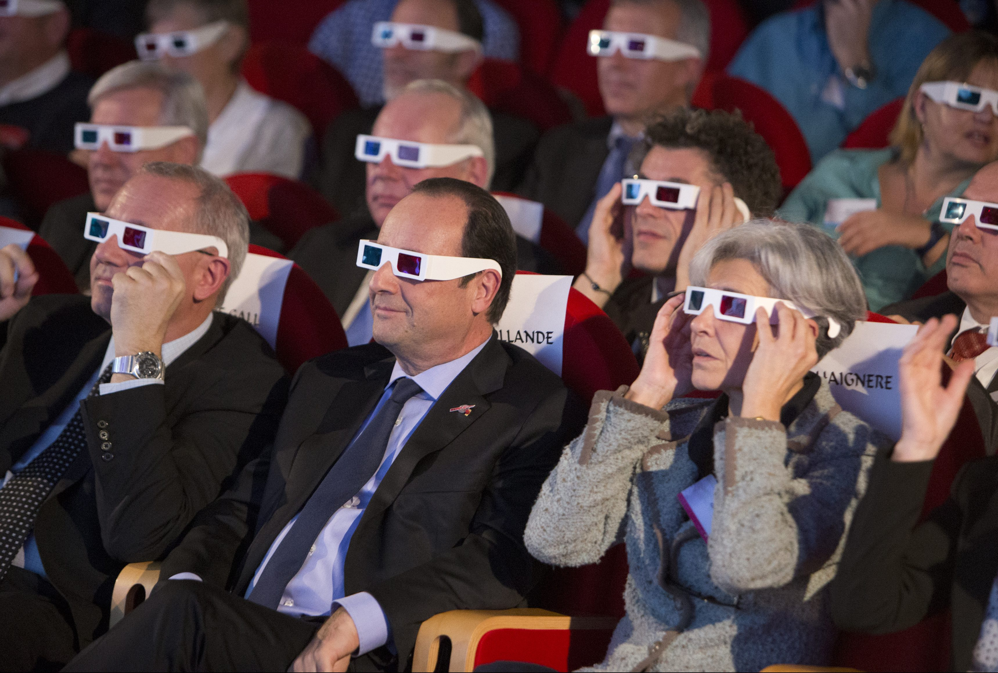 French National Centre for Space Studies (CNES) president Jean-Yves Le Gall (L) French President Francois Hollande (C) and former French astronaut Claudie Haignere wear 3D glasses during a visit at the Cite des Sciences at La Villette in Paris as they follow the successful landing of the Philae lander on comet 67P/ Churyumov-Gerasimenko, November 12, 2014. The European Space Agency's (ESA) landed a probe on a comet on Wednesday, a first in space exploration and the climax of a decade-long mission to get samples from what are the remnants of the birth of Earth's solar system.