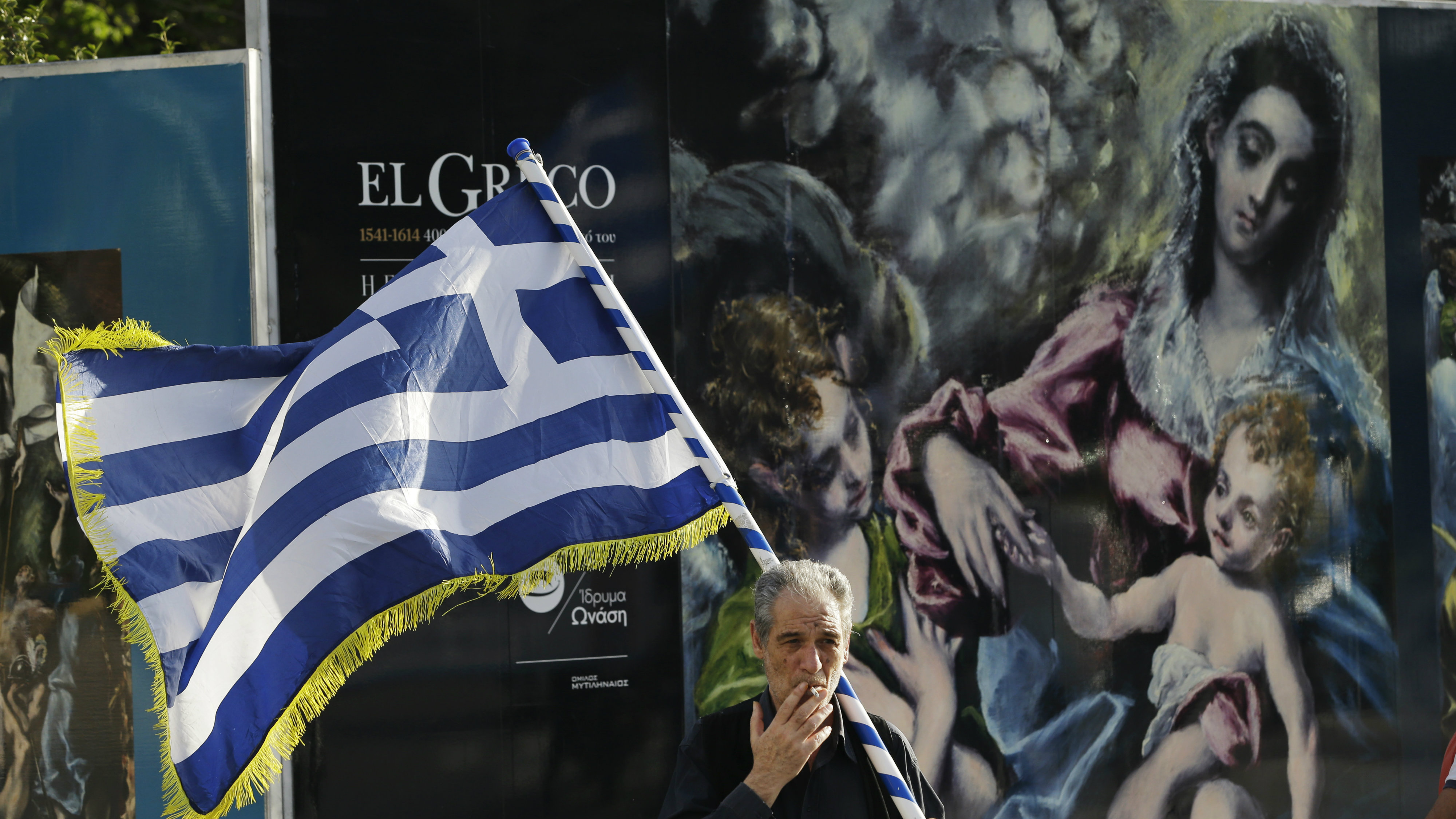 A demonstrator holding a Greek flag joins a protest against Greece's creditors in Athens April 2016