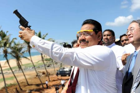 A President Media Davison handout picture shows Sri Lankan President preparing to fire a flare while special representative from China, Sang Guowei watches from behind welcoming the first ship, Sri Lanka Navy vessel Jetliner into the newly built Magampura Mahinda Rajapaksa Port which was ceremonial commissioned in Hambantota 238kms south of Colombo 18 November 2010. The first stage of the Hambantota or Magampura Mahinda Rajapaksa Port in Hambantota, build with Chinese assistance was commissioned today amidst much grandeur. Today also marks President Percy Mahendra ?Mahinda? Rajapaksa?s 65th birthday. He is to take oaths for a second term as president of the island nation tomorrow (Nov. 19) and several events are being held in commemoration.