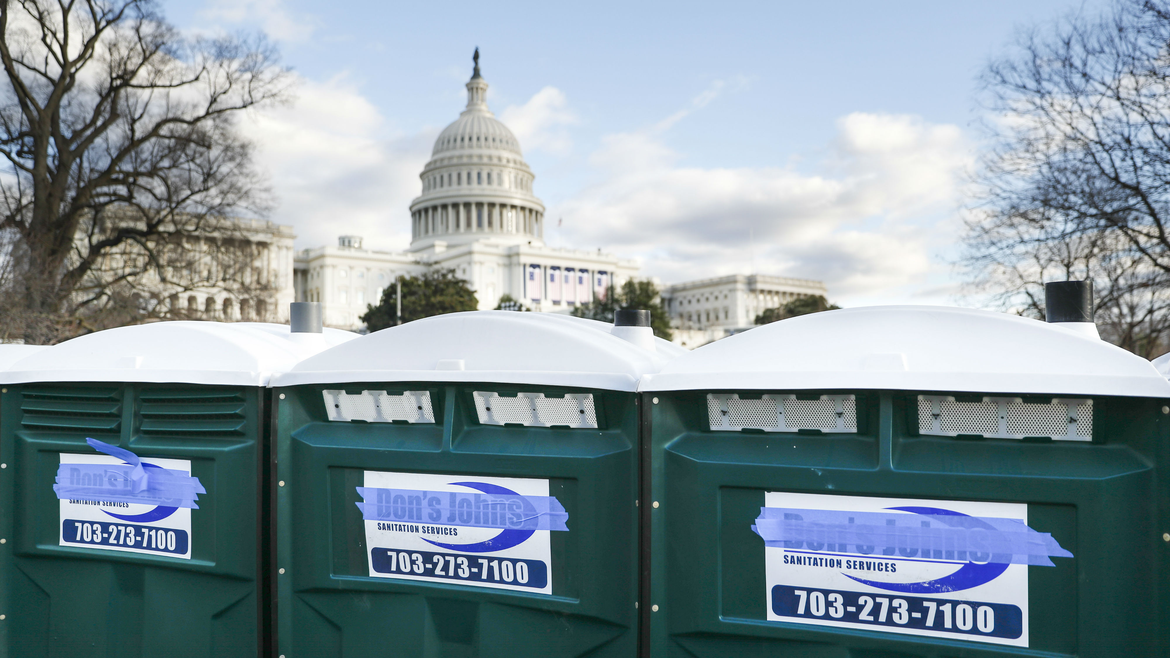 Three port-a-potties outside of the US Capitol. The logo of their company—Don's John's—has been covered with blue tape.