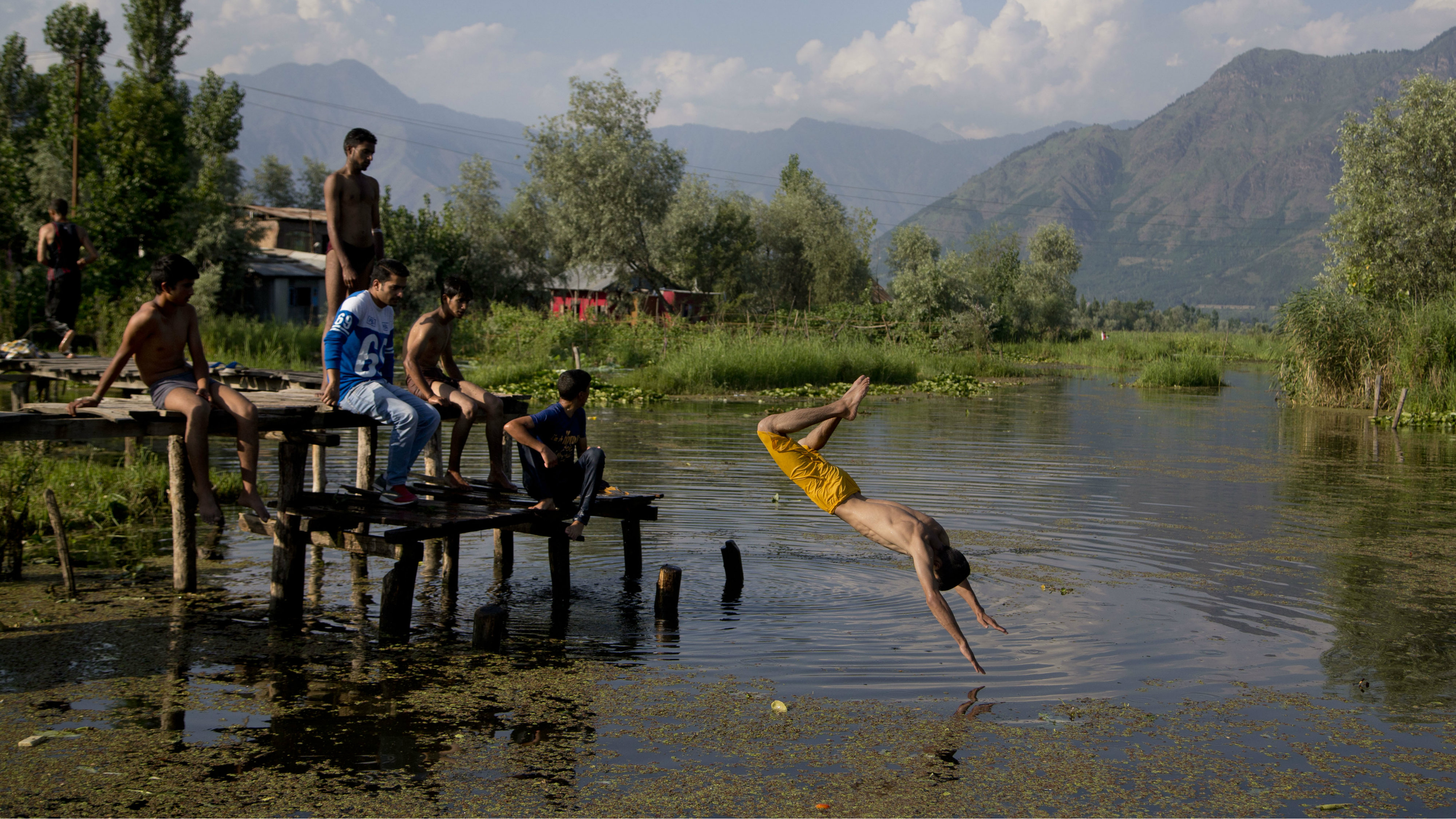 A Kashmiri boy dives into the Dal Lake in Srinagar, Indian controlled Kashmir, Thursday, June 30, 2016. Nestled in the Himalayan mountains and known for its beautiful lakes and saucer-shaped valleys, the Indian portion of Kashmir, is also one of the most militarized places on earth.