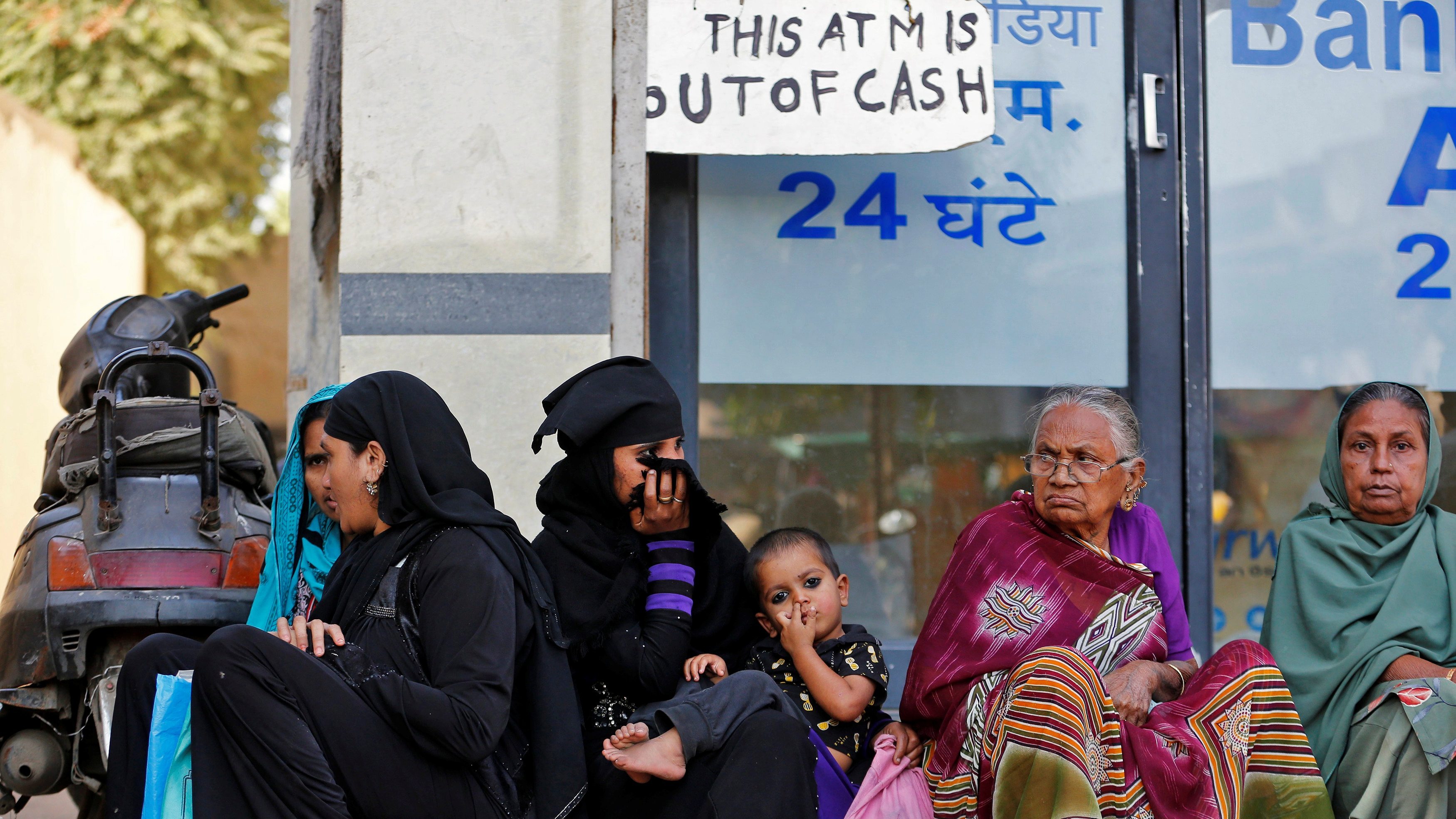 Women sit outside a bank as they wait for their turn to deposit or withdraw cash in Ahmedabad, India, November 29, 2016.  - RTSTT90