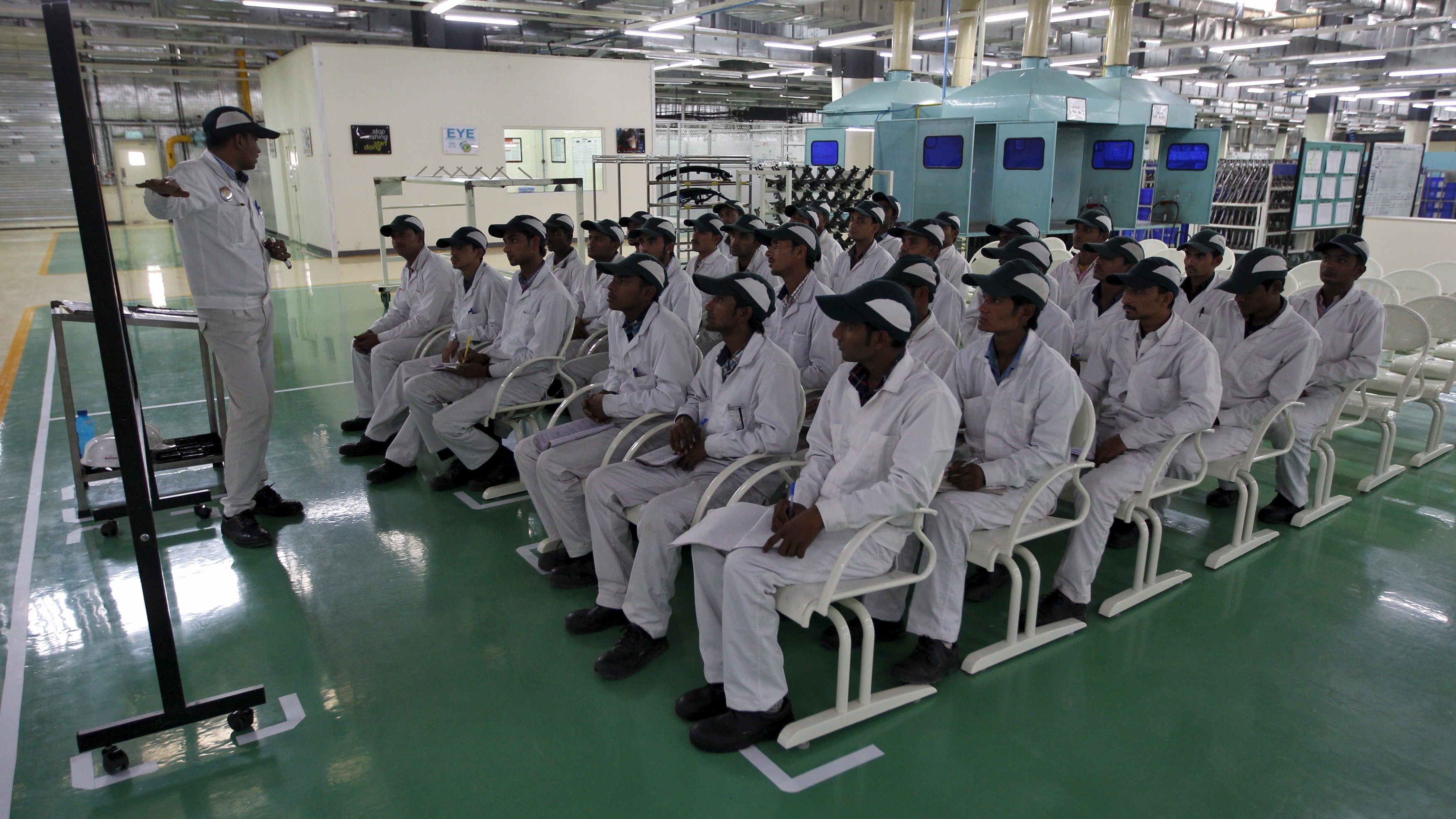An instructor teaching newly appointed workers during a media tour to the newly inaugurated Honda Motorcycle & Scooter India plant at Vithalapur