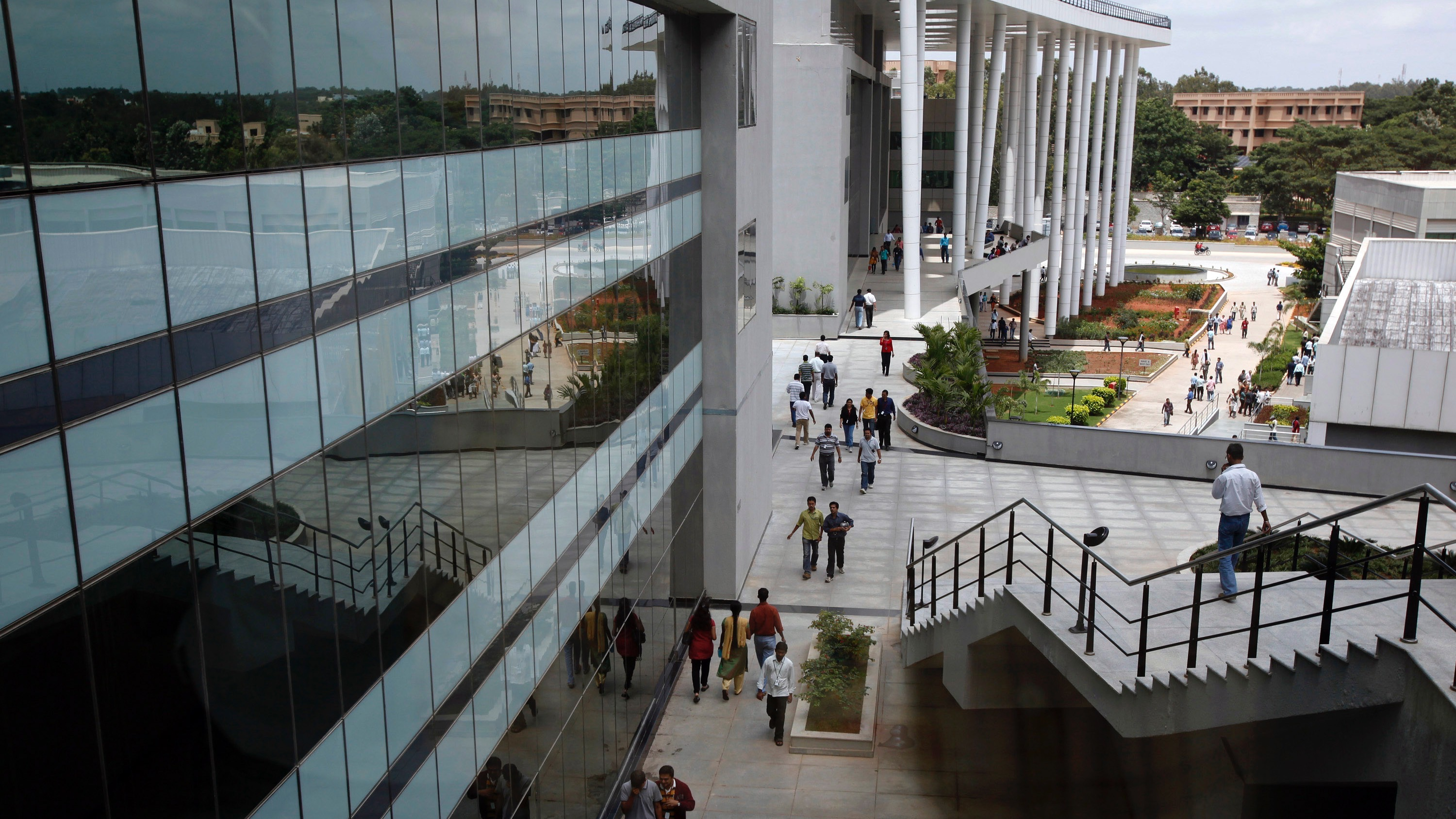 Indian software services firm Wipro Ltd. employees walk inside the company campus in Bangalore, India, Friday, July 23, 2010. Wipro Ltd. said quarterly profit jumped 31 percent to 13.19 billion rupees ($284 million), beating expectations, as India's No. 3 outsourcer ramped up staffing to meet strong global demand.