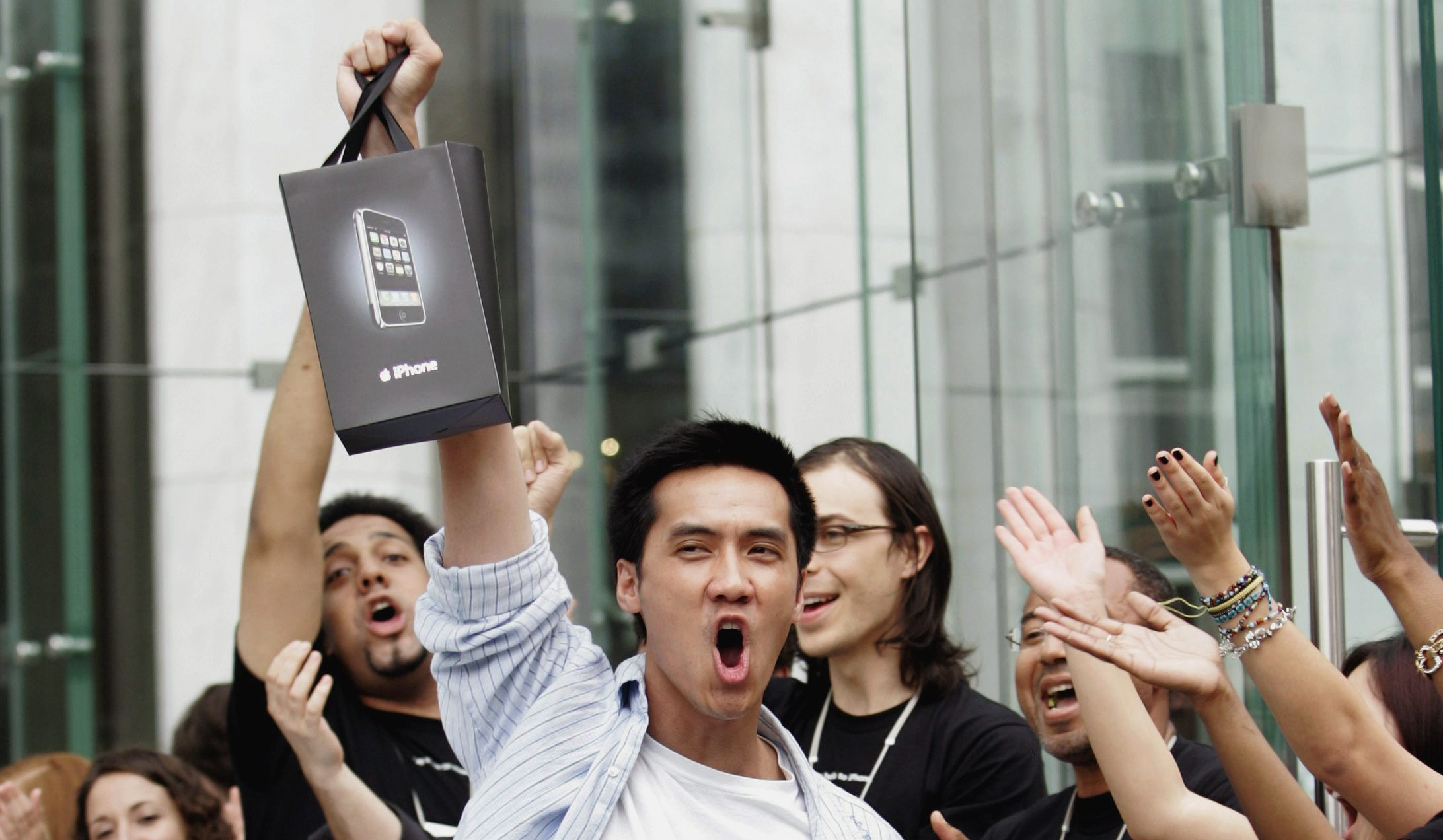 Surrounded by cheering Apple Store employees, one of the first iPhone buyers leaves the store on Fifth Avenue in New York, June 29, 2007.