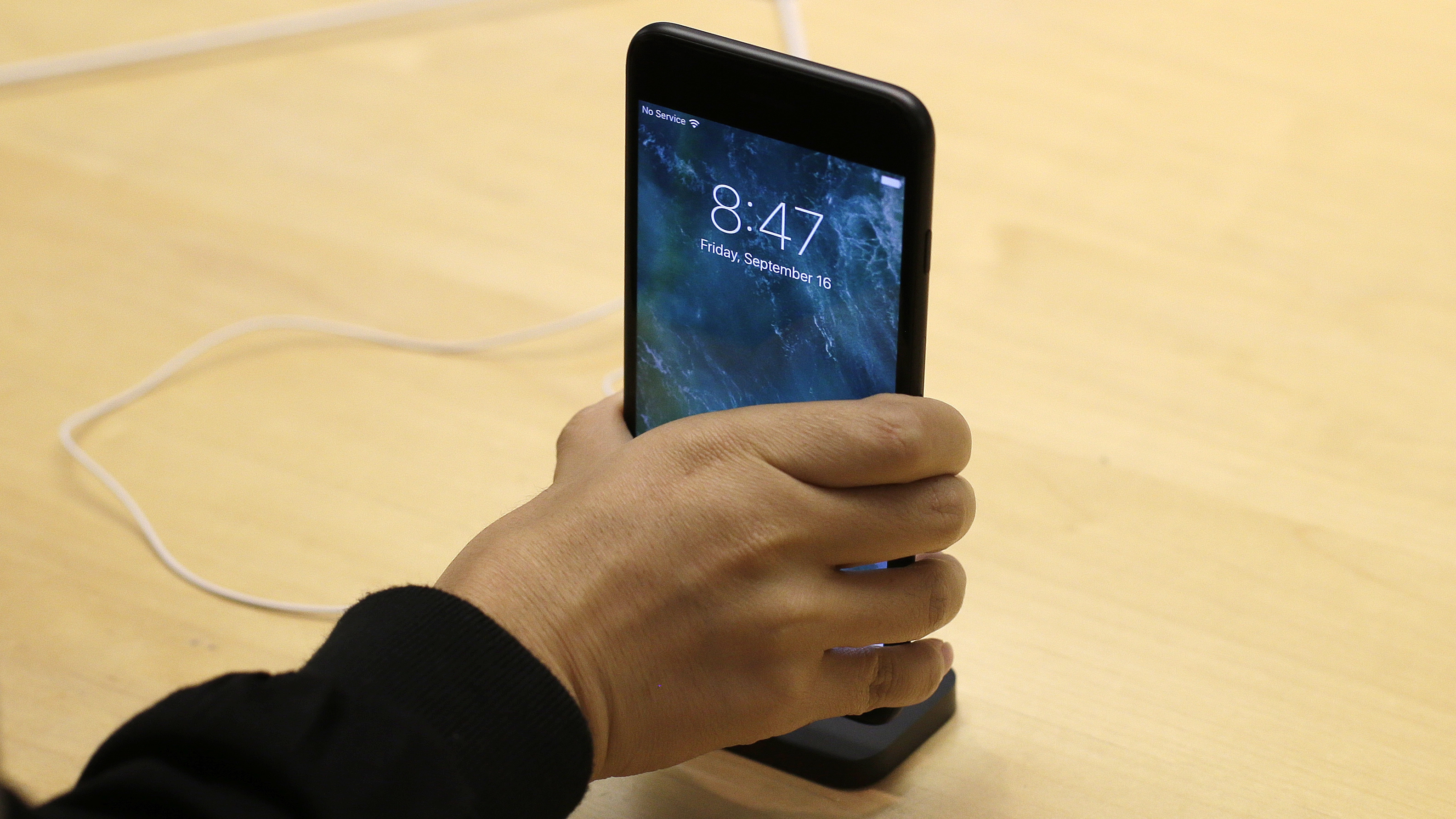 A customer checks out the new iPhone 7 Plus at the Apple Store on Michigan Avenue, Friday, Sept. 16, 2016, in Chicago. (AP Photo/Kiichiro Sato)