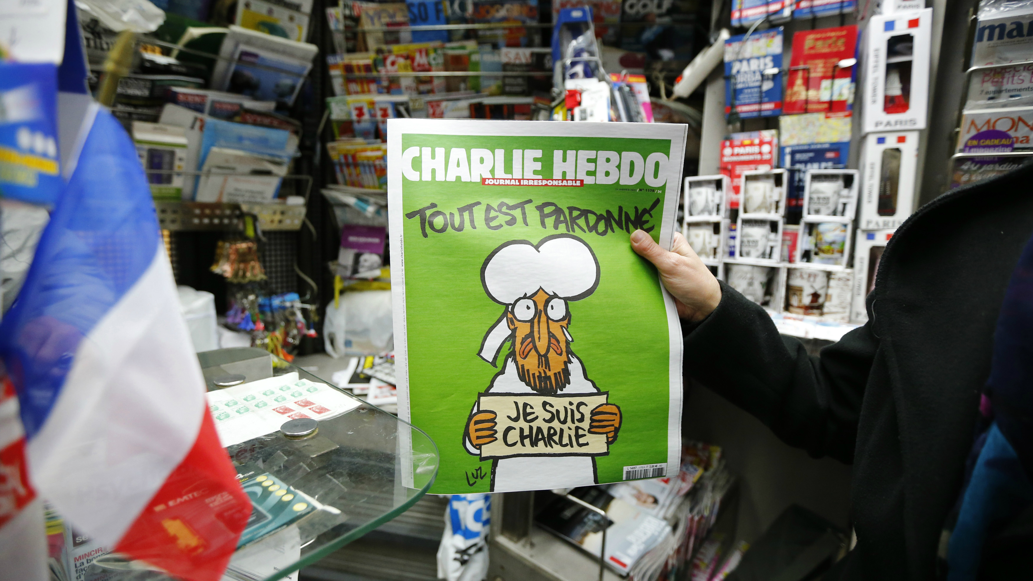 "ATTENTION EDITORS - THIS PICTURE MAY OFFEND SOME PEOPLE  A man holds the new issue of satirical French weekly Charlie Hebdo entitled ""Tout est pardonne"" (""All is forgiven""), which shows a caricature of Prophet Mohammad, in front of a kiosk in Paris January 14, 2015. The first edition of Charlie Hebdo published after the deadly attacks by Islamist gunmen sold out within minutes at newspaper kiosks around France on Wednesday, with people queuing up to buy copies to support the satirical weekly. A print run of up to three million copies has been set for what has been called ""the survivors' edition,"" dwarfing the usual 60,000 run. REUTERS/Stephane Mahe (FRANCE - Tags: CRIME LAW MEDIA) TEMPLATE OUT"