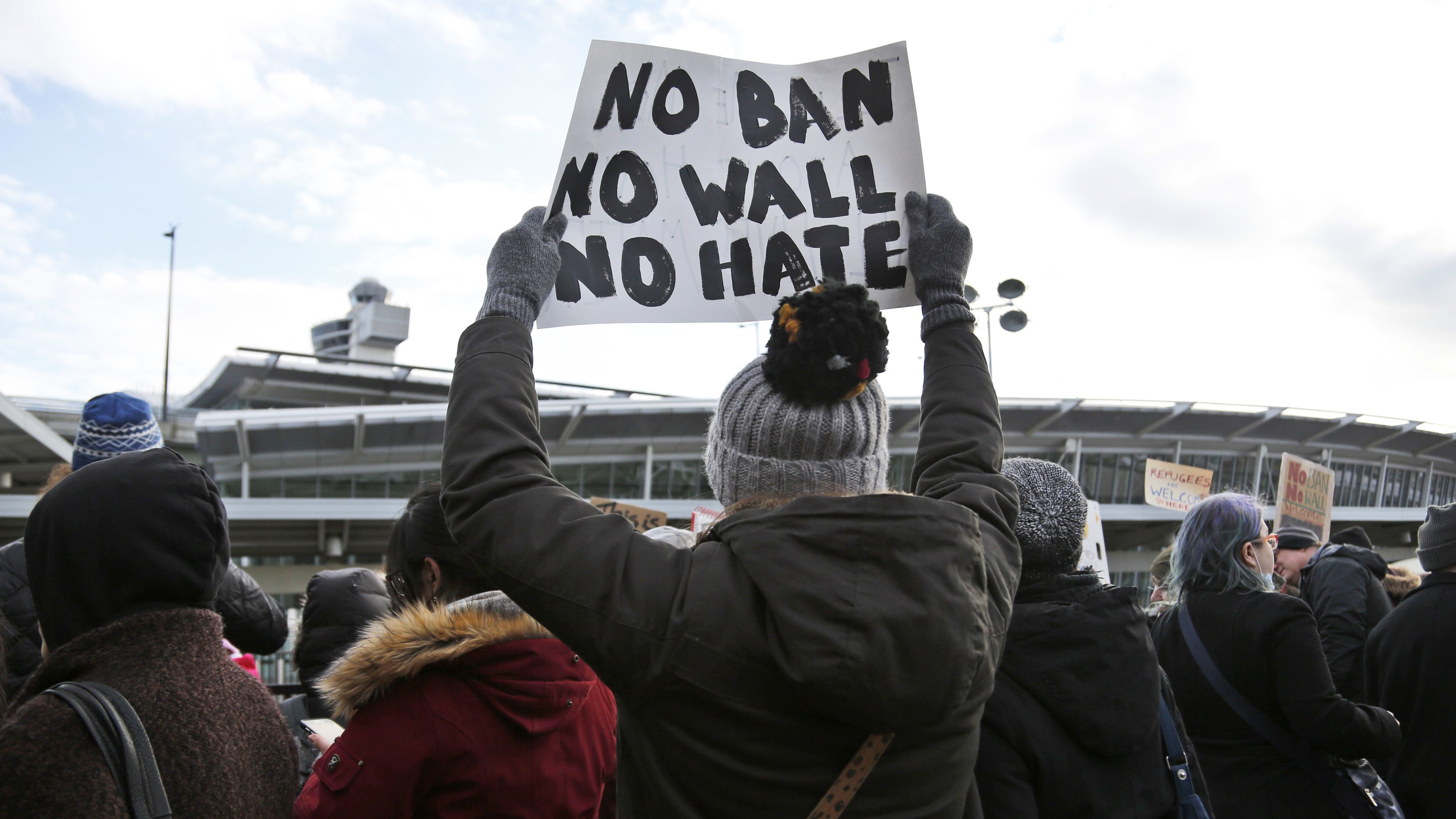 Protesters rally in front of John F. Kennedy International Airport in New York, Sunday, Jan. 29, 2017. President Donald Trump's immigration order sowed more chaos and outrage across the country Sunday, with travelers detained at airports, panicked families searching for relatives and protesters registering opposition to the sweeping measure that was blocked by several federal courts. (AP Photo/Seth Wenig)