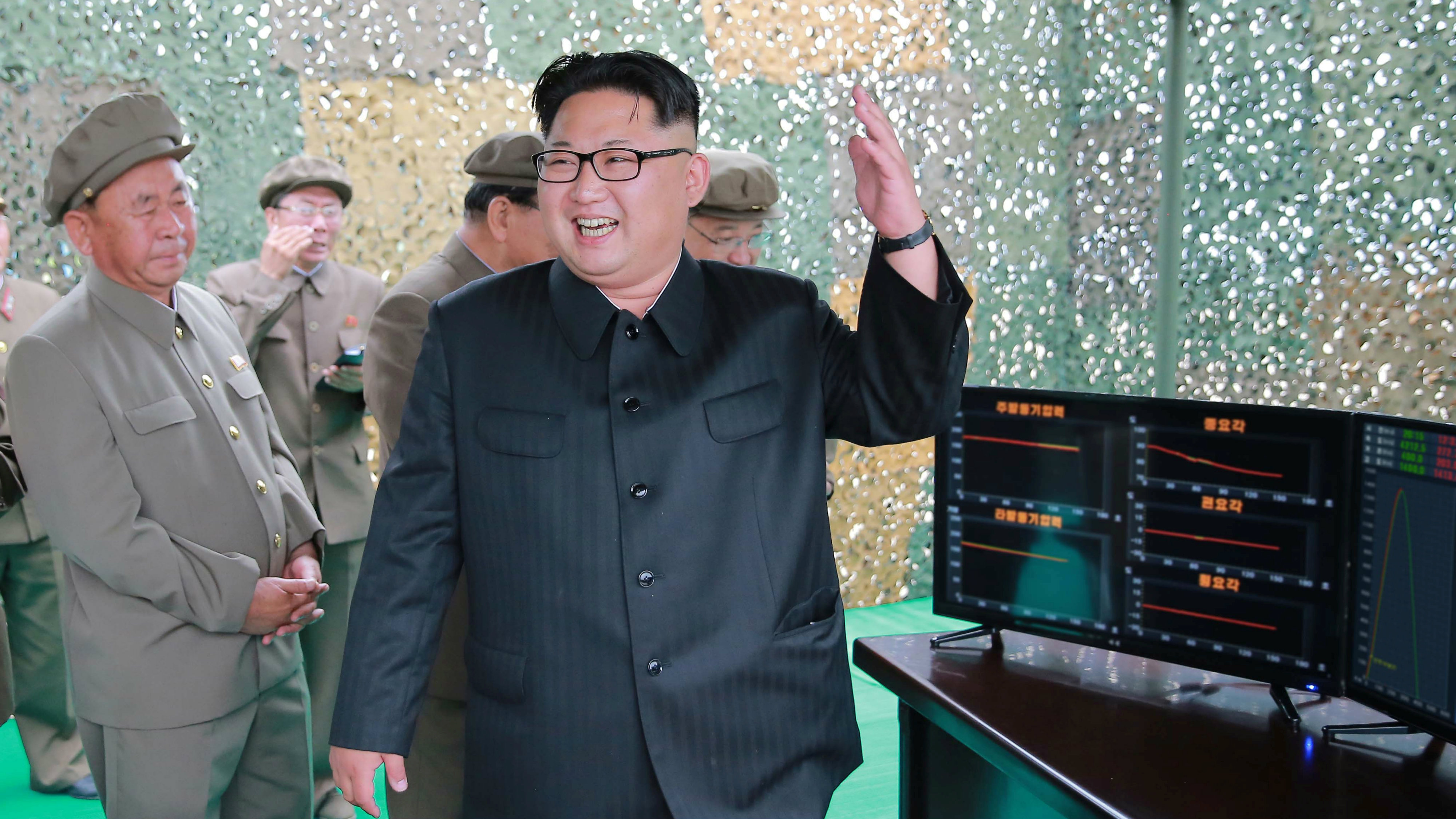 North Korean leader Kim Jong Un reacts during a test launch of ground-to-ground medium long-range ballistic rocket Hwasong-10 in this undated photo released by North Korea's Korean Central News Agency