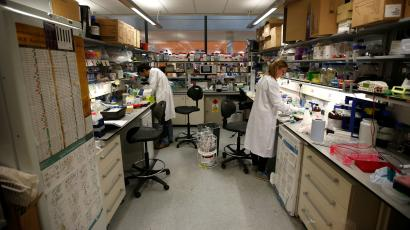 Two scientists in white coats perform cancer research.