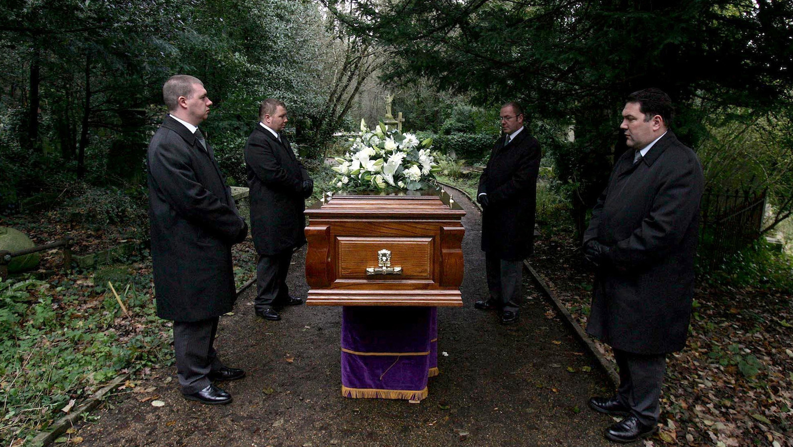 Coffin bearers stand with the coffin of former Russian spy Alexander Litvinenko during his funeral at Highgate Cemetery in London December 7, 2006. Russian prosecutors launched their own murder investigation on Thursday into the death in London from radiation poisoning of Russian ex-spy Litvinenko, in parallel to a British probe already under way. REUTERS/Cathal McNaughton/Pool (BRITAIN) - RTR1K5K4