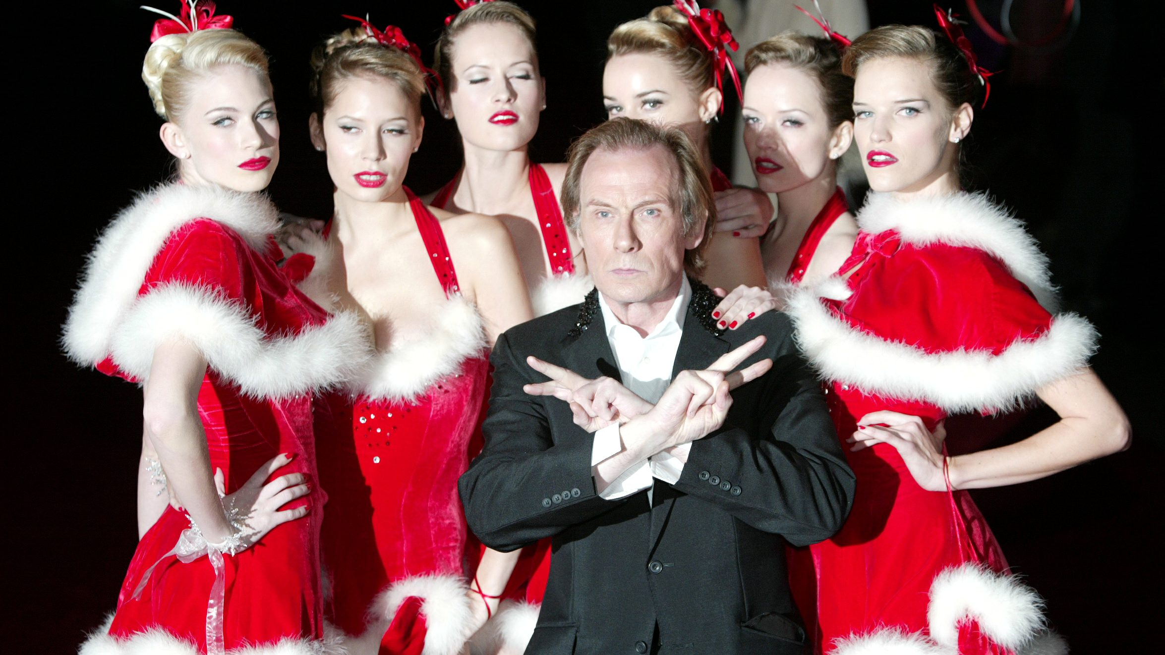 Bill Nighy accompanied by six models arrives for the UK charity premiere of 'Love Actually' in Leicester Square, London November 16, 2003.