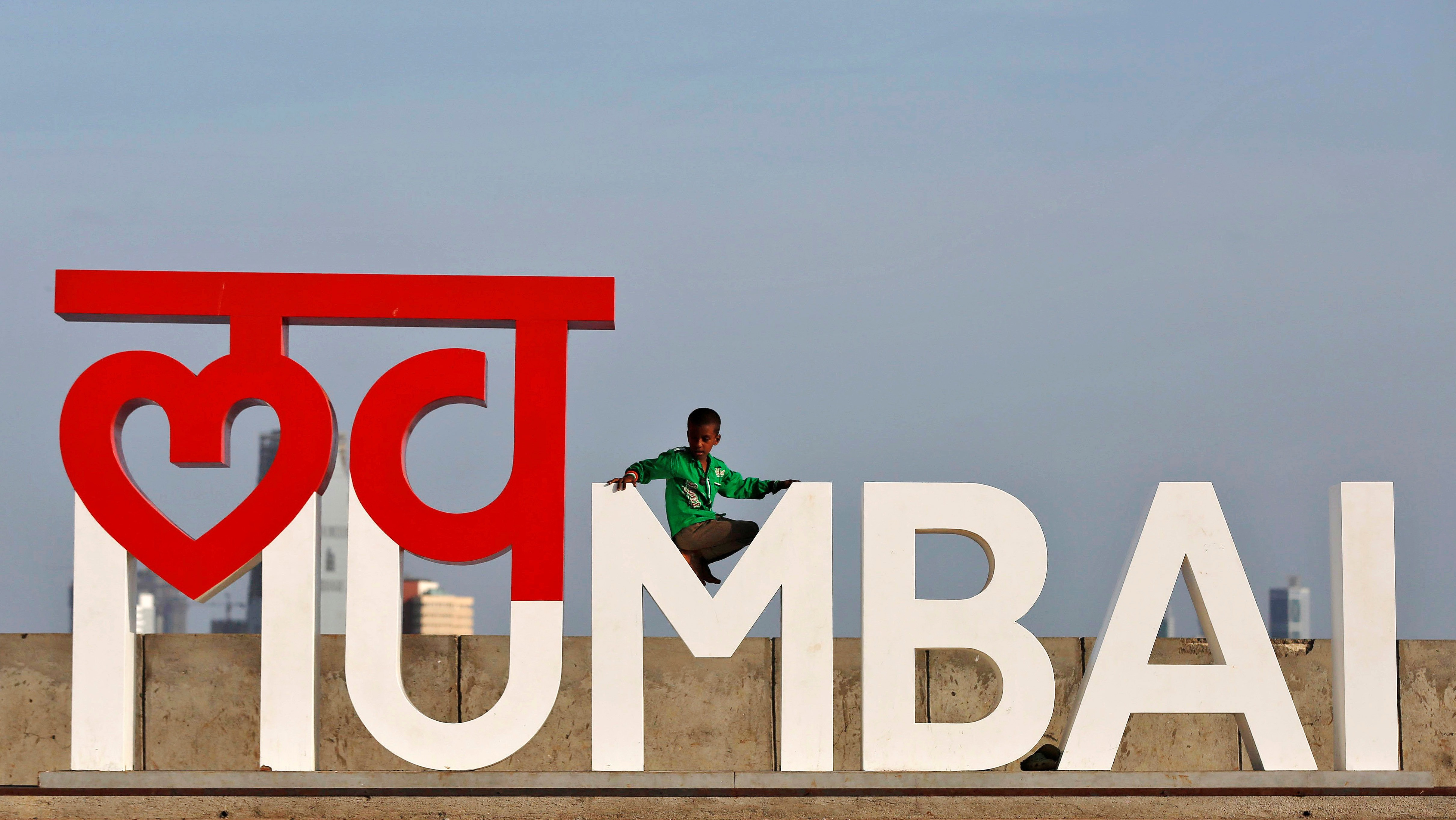 A boy plays on an installation at a wall along the sea front promenade in Mumbai