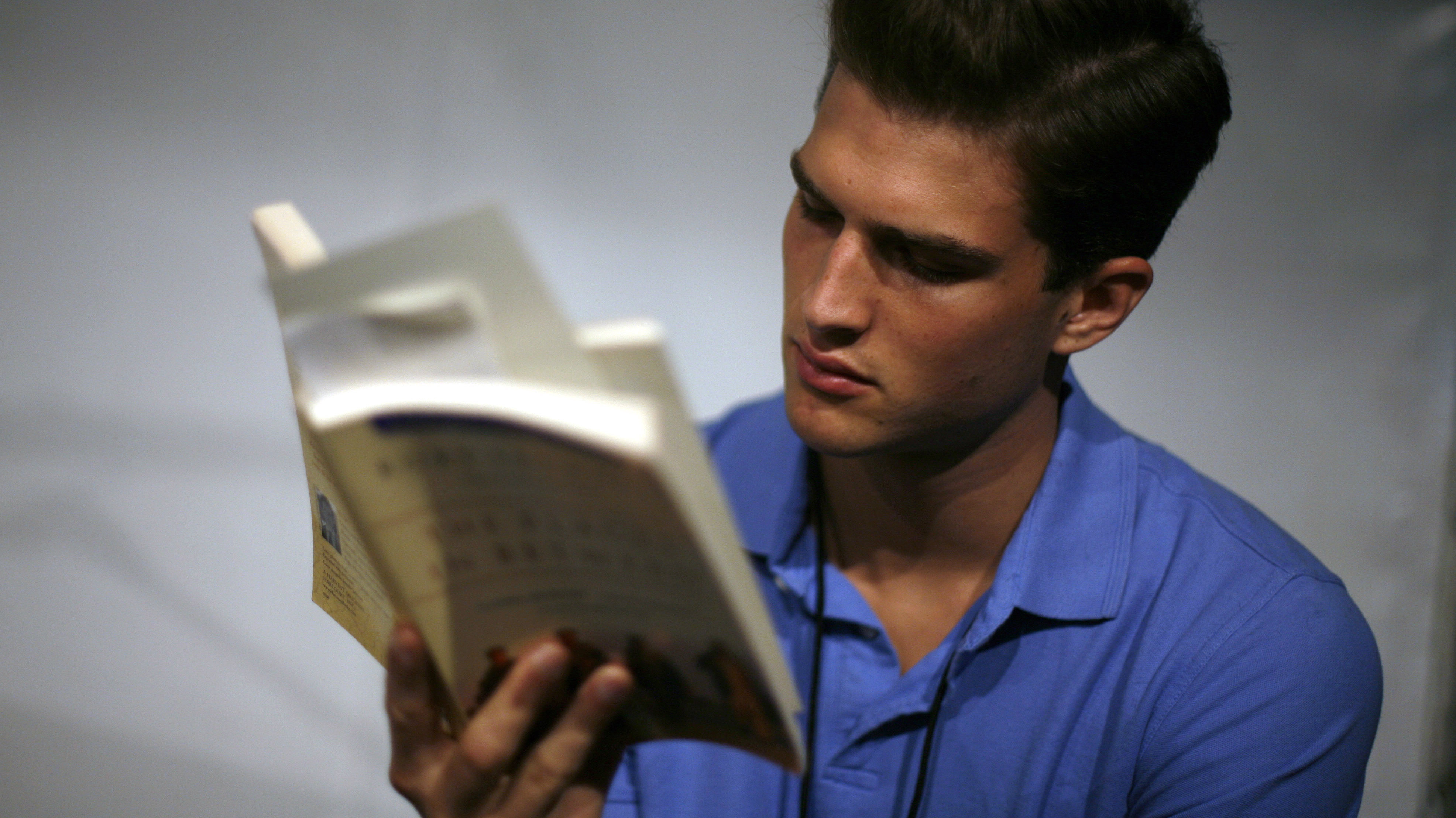 A model reads a book prior to the Spring 2008 Duckie Brown collection during New York Fashion Week September 5, 2007. REUTERS/Eric Thayer (UNITED STATES)
