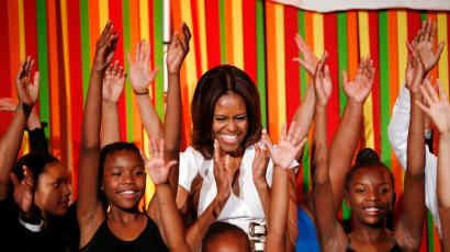 Michelle Obama smiles surrounded by children at a talent show