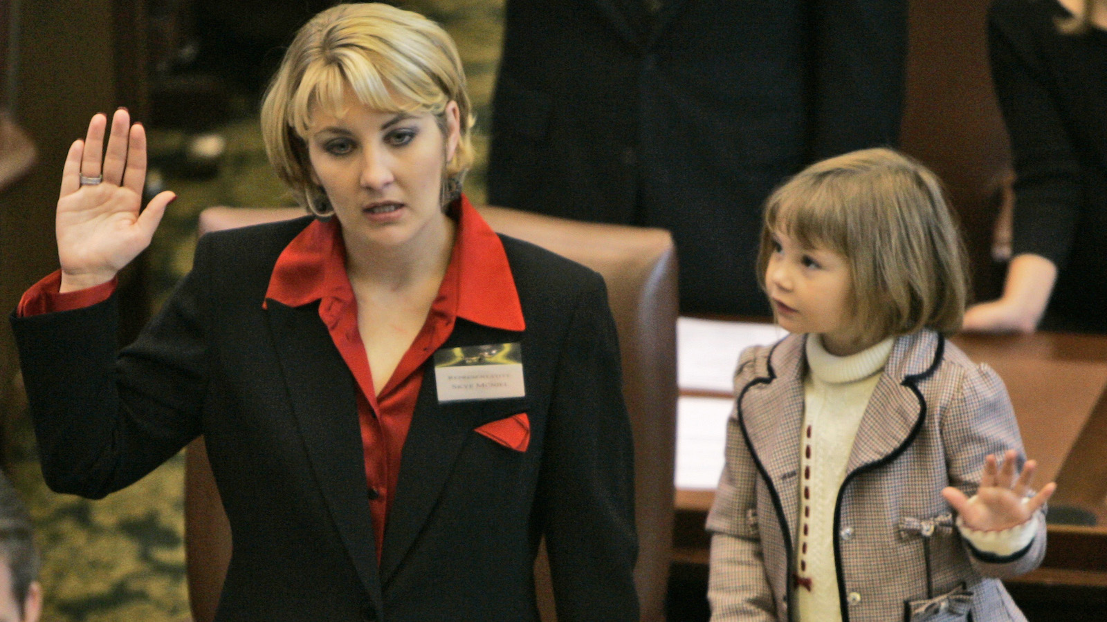 Paike Marie McNiel, right, mimics her mom, newly elected Oklahoma state Rep. Skye McNiel, left, R-Bristow, as she takes her oath of office on the House floor at the state Capitol in Oklahoma City, Thursday, Nov. 16, 2006.