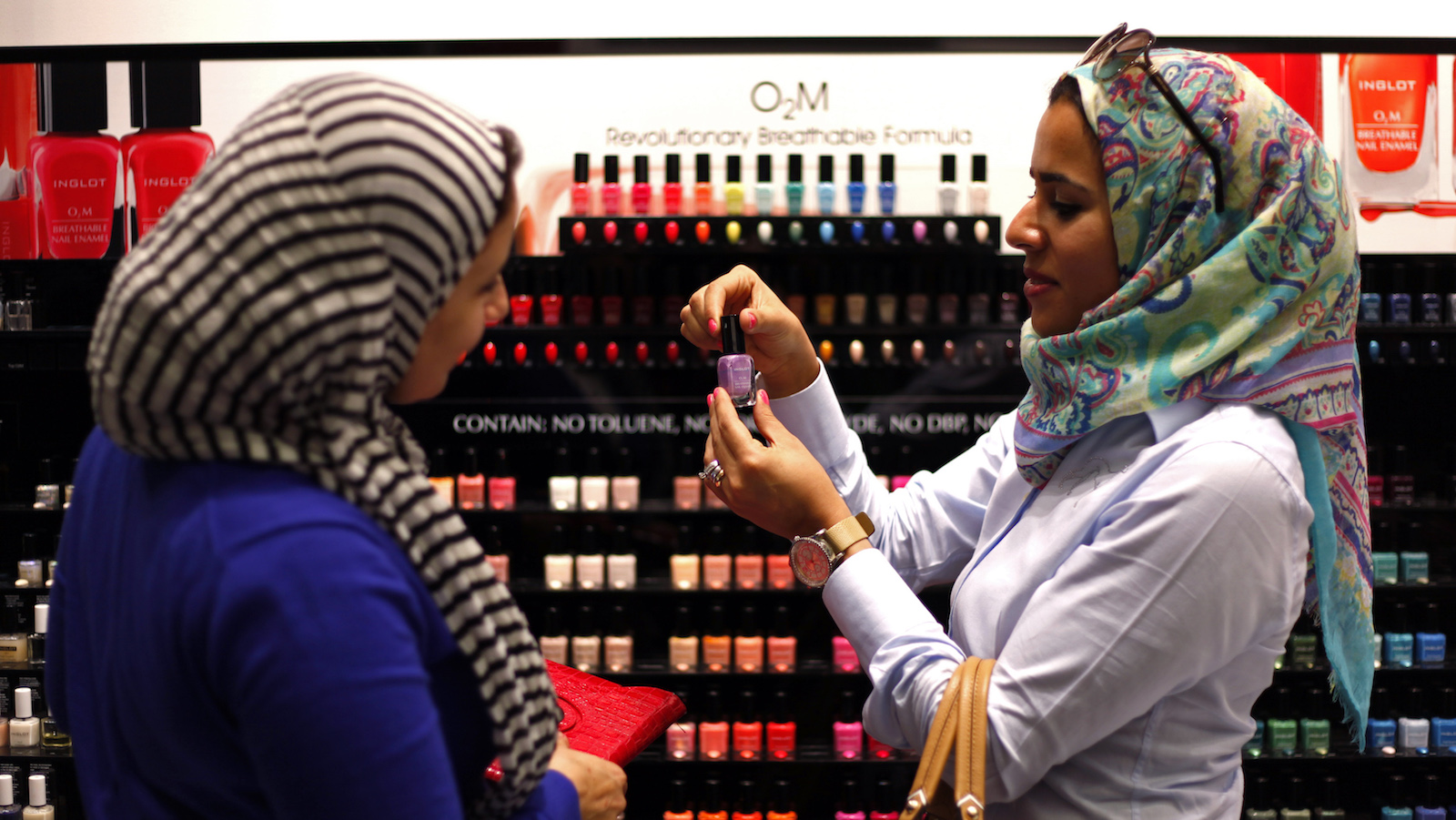 "Two Egyptian women buy ""breathable"" nail polish from a store in a Dubai shopping mall November 18, 2013. From cosmetics to accommodation, travel to toothpaste, complying with religious principles is becoming big business in the Muslim world, and Dubai, better known for flamboyance and unrestrained consumerism than Islamic scholarship, sees an opportunity. The emirate is mounting the world's first systematic drive to profit from ""halal"" goods and services by setting global standards for them and providing certification where the standards are met. ""Breathable"" nail varnish claims to let moisture and oxygen pass through to the nail so the wearer can properly wash as required before prayers. Picture taken November 18.     REUTERS/Ahmed Jadallah (UNITED ARAB EMIRATES - Tags: BUSINESS FASHION RELIGION) - RTX15L9S"