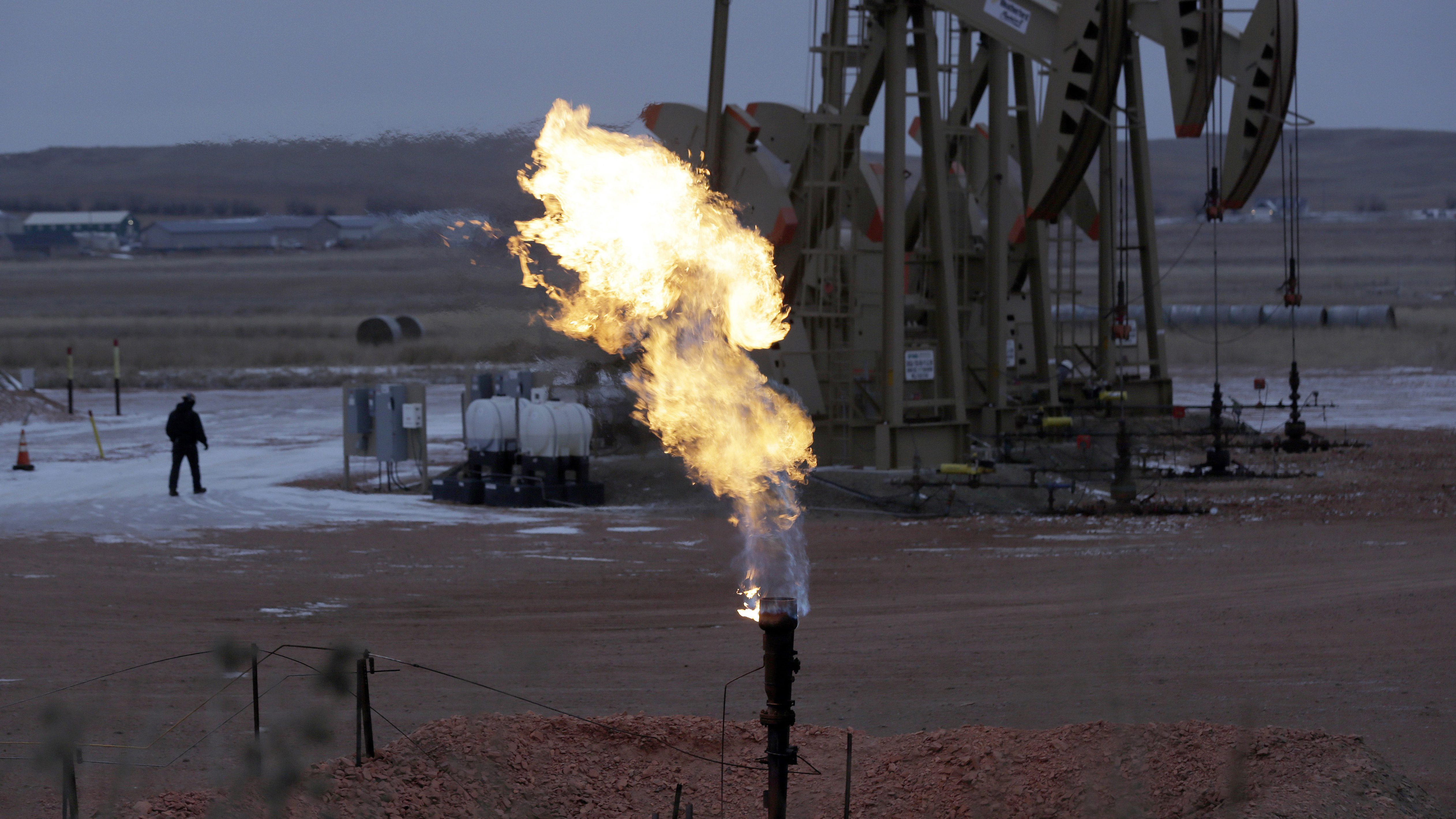 A natural gas flare is seen in front of a oil pumpjack