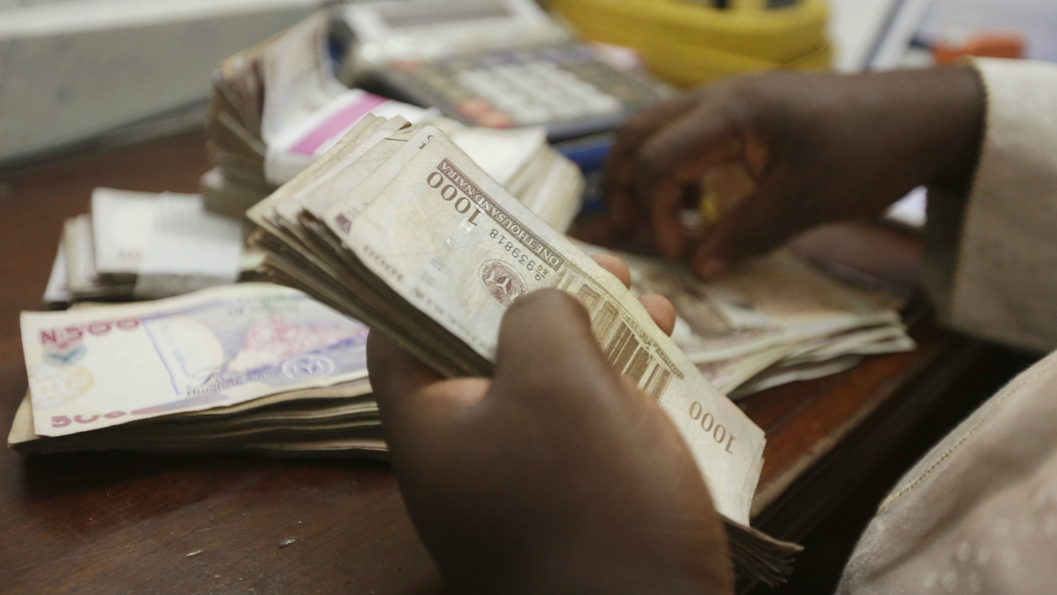 In this photo taken Tuesday Oct. 20, 2015, a money changer counts Nigerian naira currency at a bureau de change, where a dollar buys 222 naira compared to the official rate of 198, in Lagos, Nigeria. The IMF is pressing Nigeria to further devalue its naira currency amid uncertainty over the political and economic outlook for Africa's biggest oil producer and economy. Analysts said there's disappointment that President Muhammadu Buhari's long-awaited Cabinet list includes no economic stars. The naira has lost 25 percent of its value in the past year and the stock market has plummeted because of political uncertainty and halved prices for oil that provides most government revenue.
