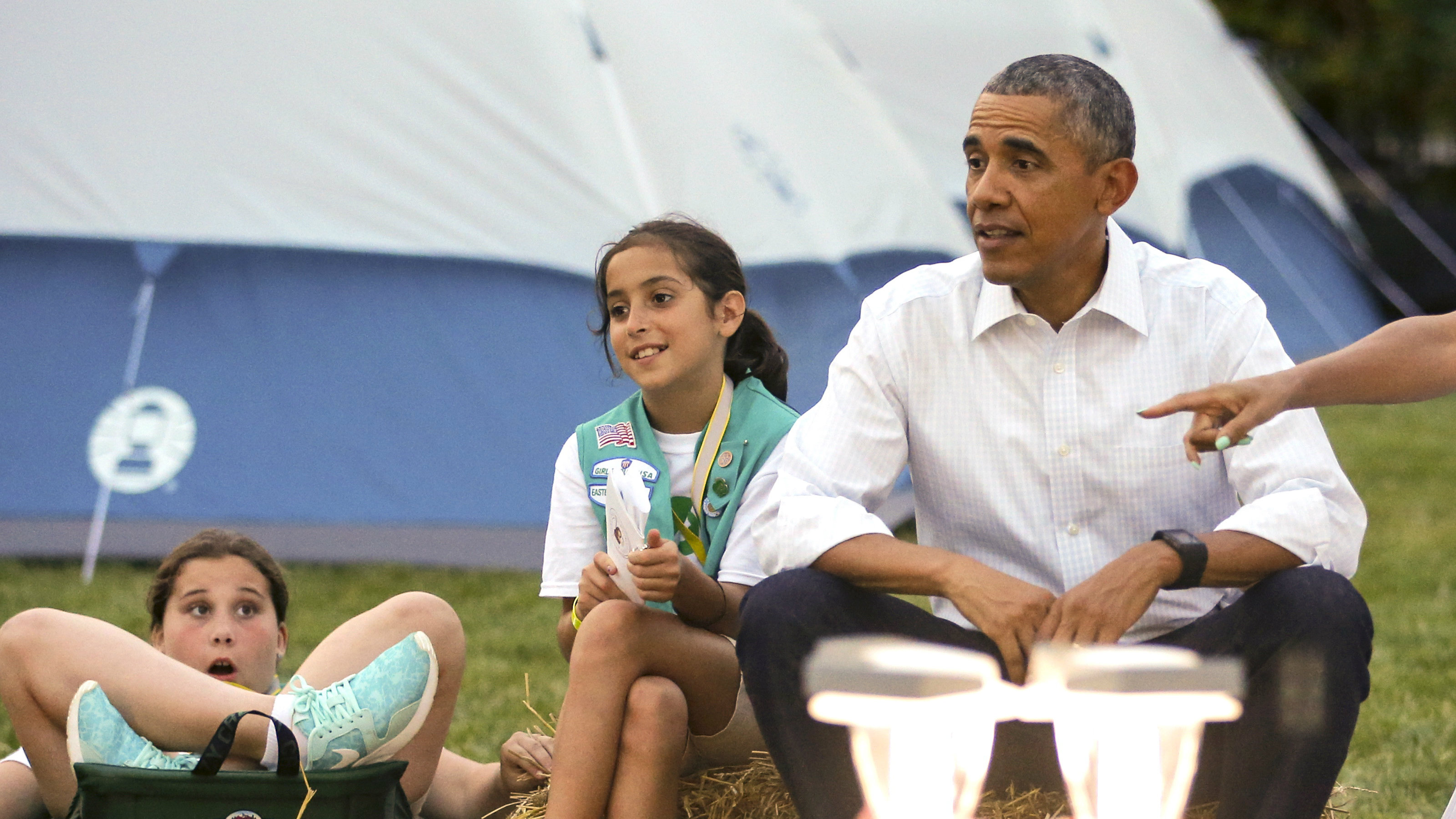 Barack Obama sitting with two girl scouts.