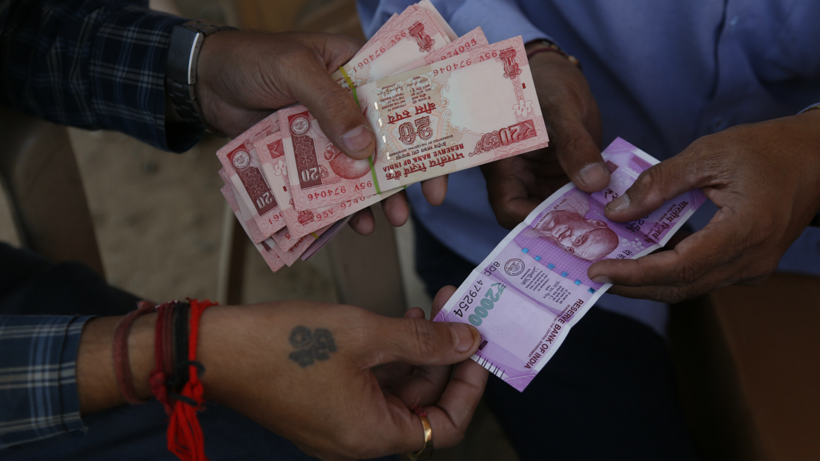 An Indian man, left, gets a high denomination currency note of Indian rupees 2000 exchanged for smaller notes at a roadside stall set up by Shri Jalaram Gaushala, a shelter for cows, in Ahmadabad, India, Friday, Nov. 18, 2016. The cow shelter is helping people change high denomination currency received from banks with the daily donations they receive in low denomination currency notes. The sudden withdrawal of 86 percent of India's currency has left cash in short supply, retail sales stumbling and wholesale markets in turmoil.