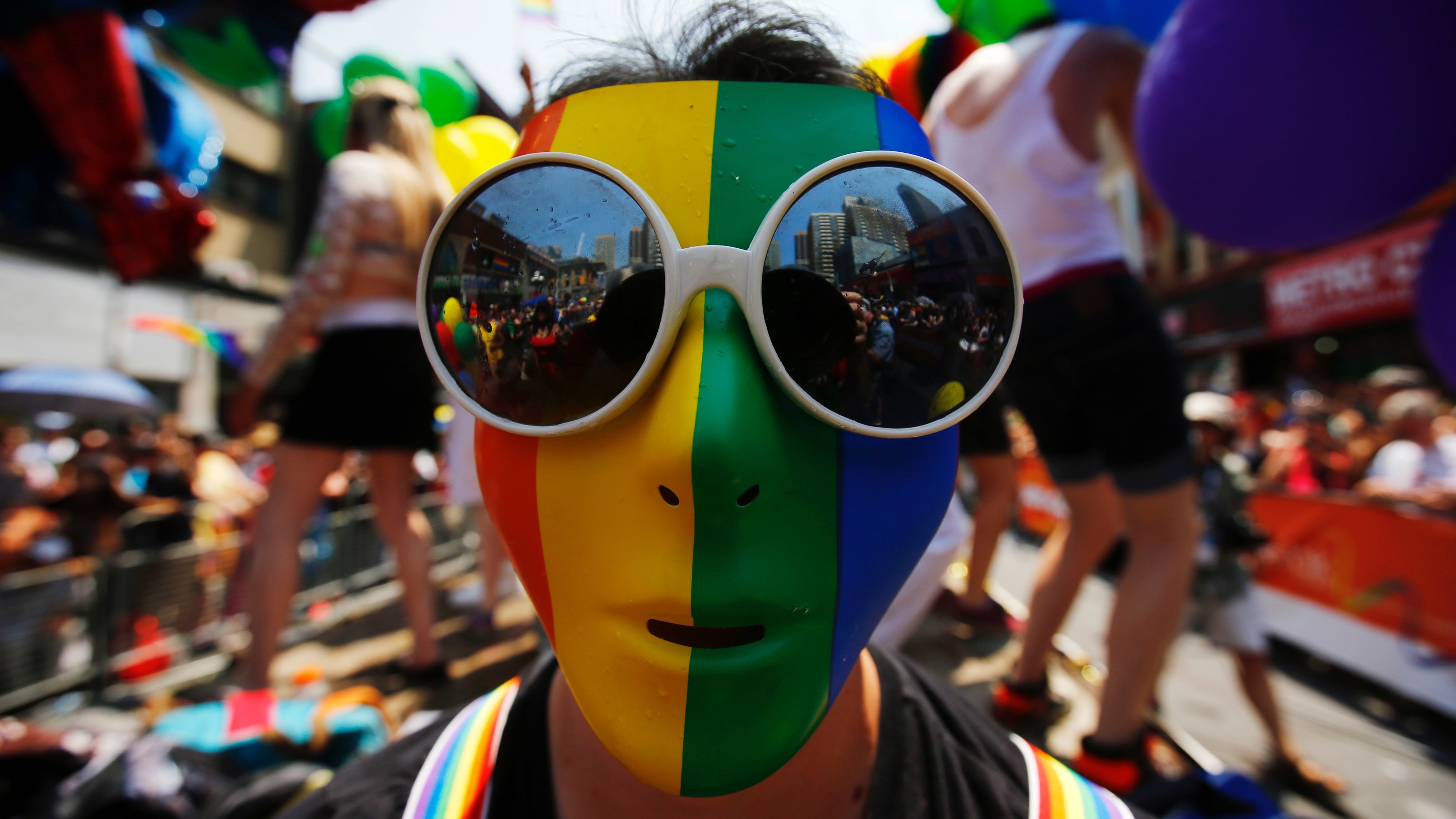 """A man wearing a rainbow mask is seen during the"""" WorldPride"""" gay pride Parade in Toronto, June 29, 2014. Toronto is hosting WorldPride, a week-long event that celebrates the lesbian, gay, bisexual and transgender (LGBT) community.    REUTERS/Mark Blinch (CANADA - Tags: SOCIETY) - RTR3WCL5"""