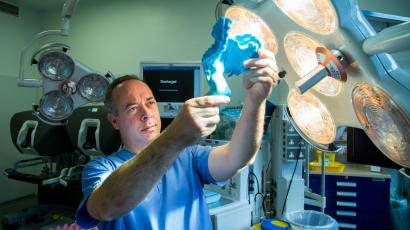 Surgeon Calvin Coffey holds up a 3D plastic model of the mesentery in an operating room.