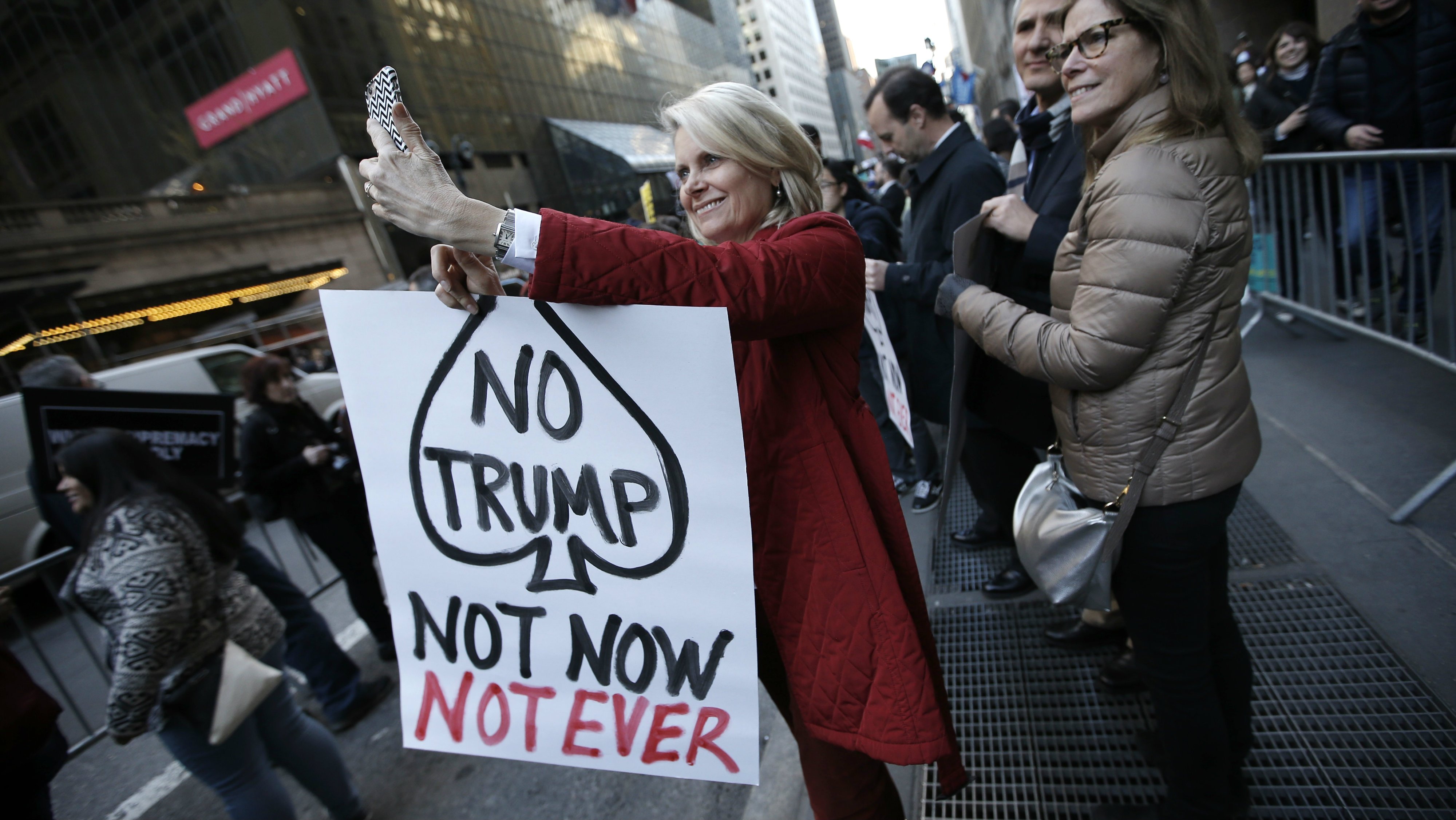 """A protester takes a """"selfie"""" while demonstrating against Republican U.S. presidential candidate Donald Trump in midtown Manhattan in New York City April 14, 2016."""