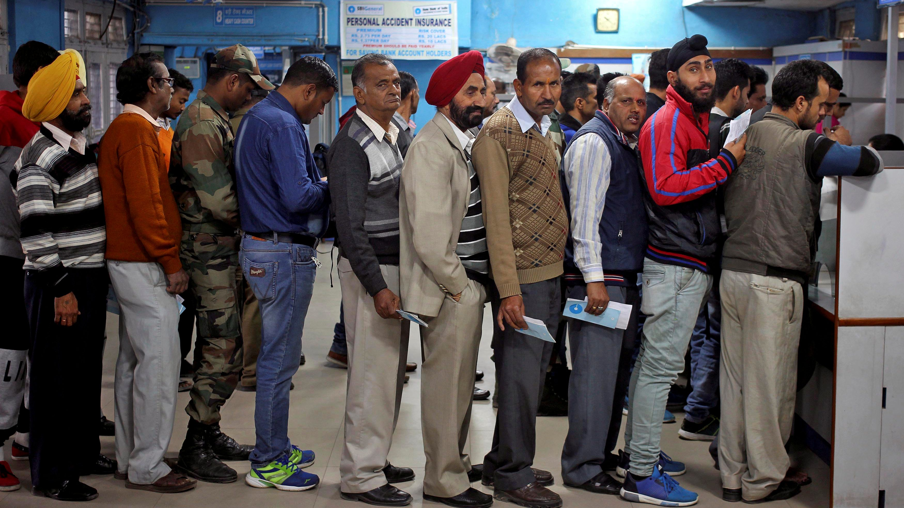 People queue as they wait for their turn to exchange or deposit their old high denomination banknotes in Jammu, November 24, 2016.