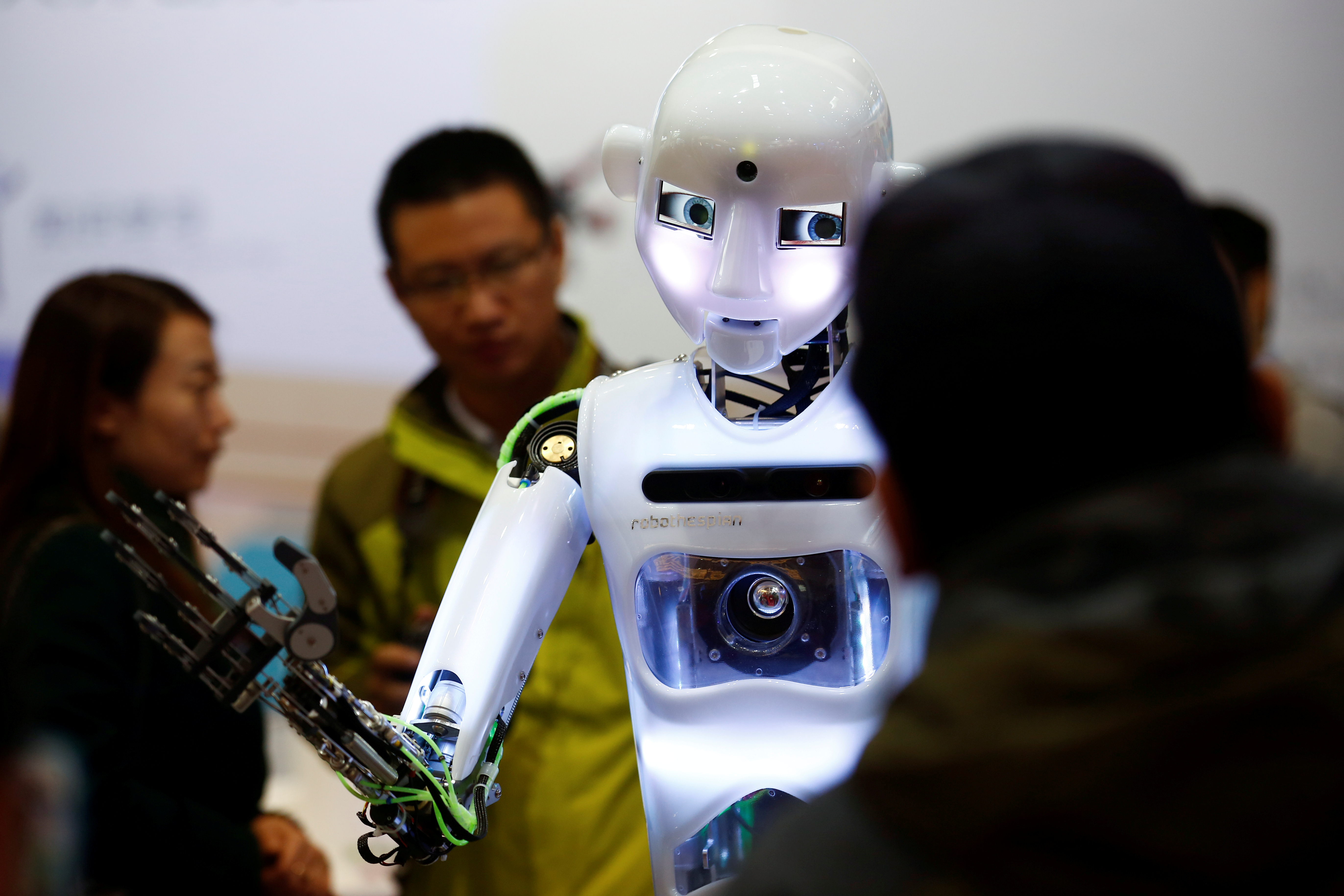 FILE PHOTO: People look at a RoboThespian humanoid robot at the Tami Intelligence Technology stall at the WRC 2016 World Robot Conference in Beijing, China, October 21, 2016.