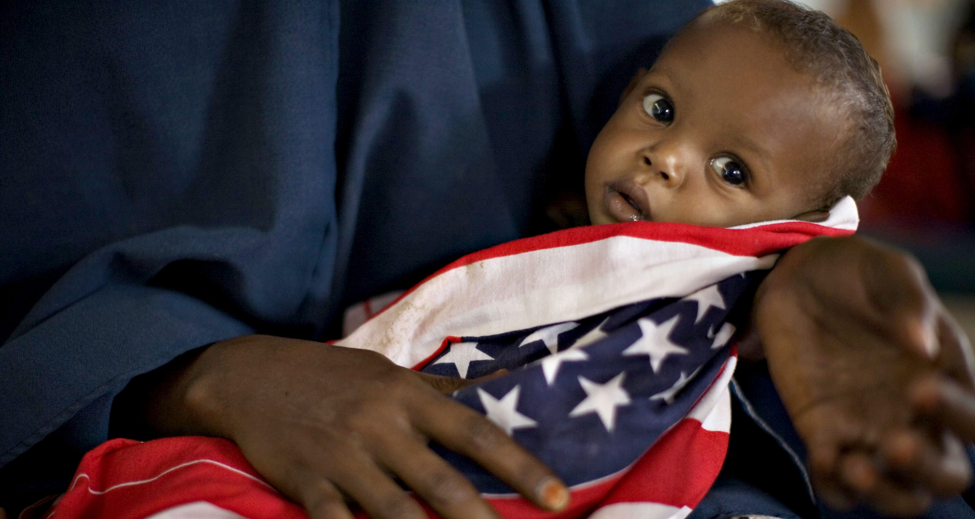 """A malnourished Somali child is wrapped in an American """"Stars and Stripes"""" cloth at a therapeutic feeding center at Dagahaley camp in Dadaab in Kenya's northeastern province, June 8, 2009. Weeks of intense fighting in Somalia has driven mor than 100,000 people from their homes, swelling camps on the Kenyan border that are already the largest and oldest in the world, sheltering more than 270,000 Somali refugees. Picture taken June 8, 2009."""