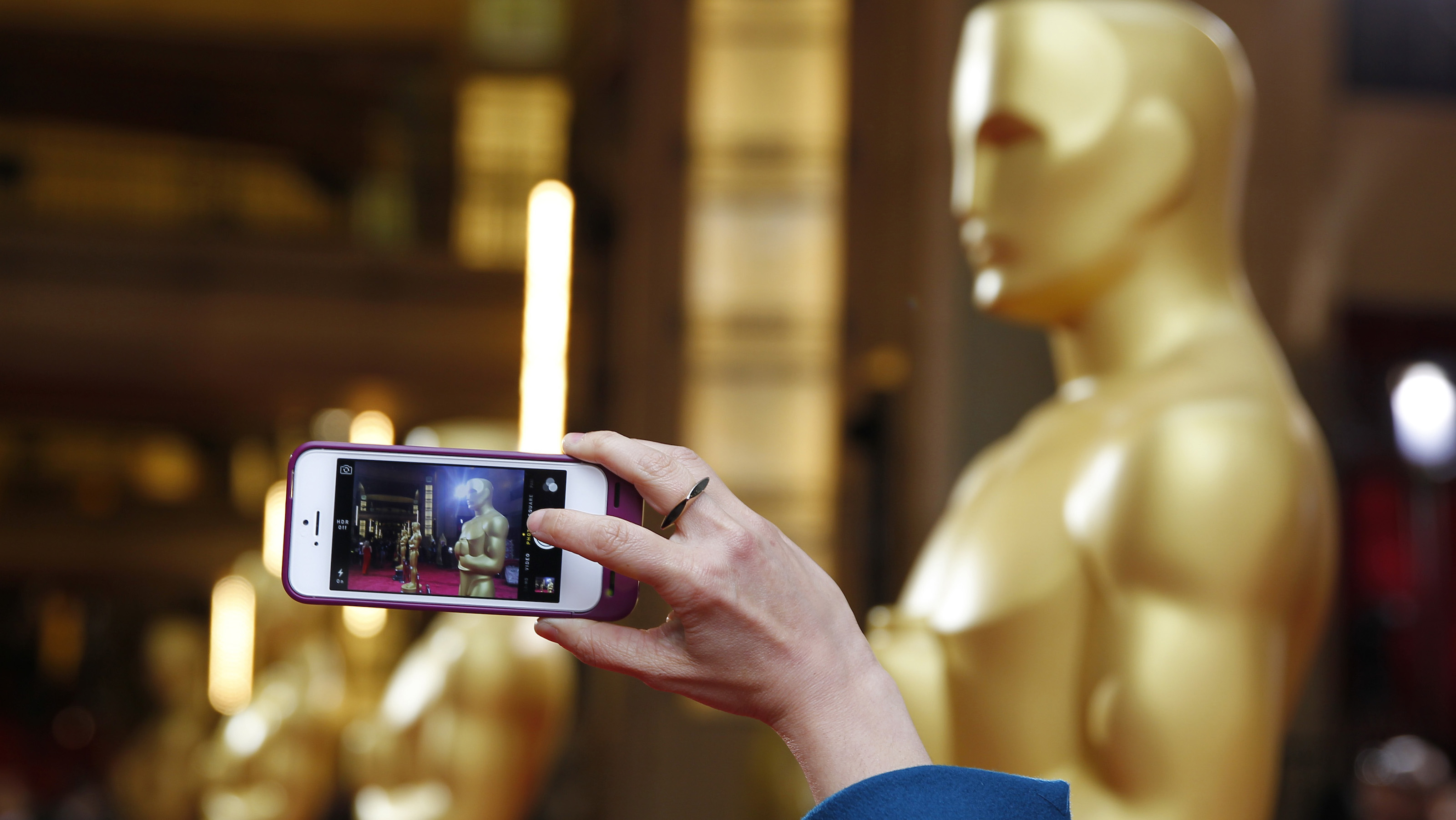 A person uses a phone to take a picture of an Oscars statue at the 86th Academy Awards in Hollywood, California March 2, 2014.  REUTERS/Mike Blake (UNITED STATES TAGS: ENTERTAINMENT) (OSCARS-ARRIVALS)   - RTR3FXA1