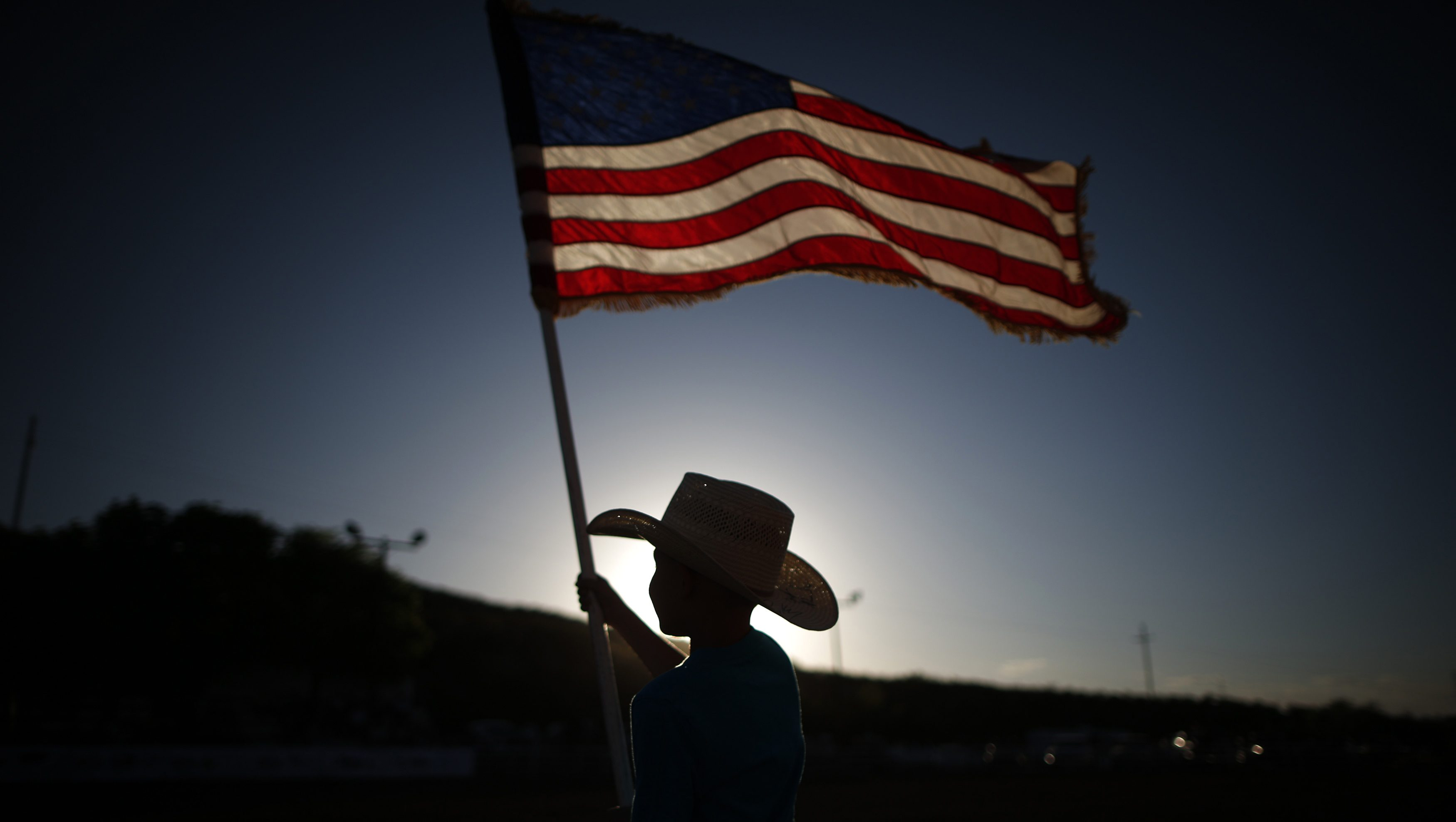 Esteban Edwards, 7, holds a U.S. flag at the rodeo in Truth or Consequences, New Mexico May 3, 2014.  The world's first purpose-built commercial space base and soon-to-be site of the first space flights with Sir Richard Branson's Virgin Galactic is near the town of Truth or Consequences in New Mexico. The inaugural flight into suborbital space should happen later this year and the first astronauts, who have made reservations and paid $250,000 for the flight, should follow a month later. While it's not clear what the economic impact will be, many agree that Spaceport America should inject new energy into the town. Picture taken May 3, 2014.      REUTERS/Lucy Nicholson (UNITED STATES - Tags: BUSINESS SOCIETY SCIENCE TECHNOLOGY TPX IMAGES OF THE DAY)  ATTENTION EDITORS: PICTURE 40 OF 40 FOR PACKAGE 'TRUTH OR CONSEQUENCES - SPACEPORT'. TO FIND ALL IMAGES SEARCH 'CONSEQUENCES LUCY' - RTR3OAR0