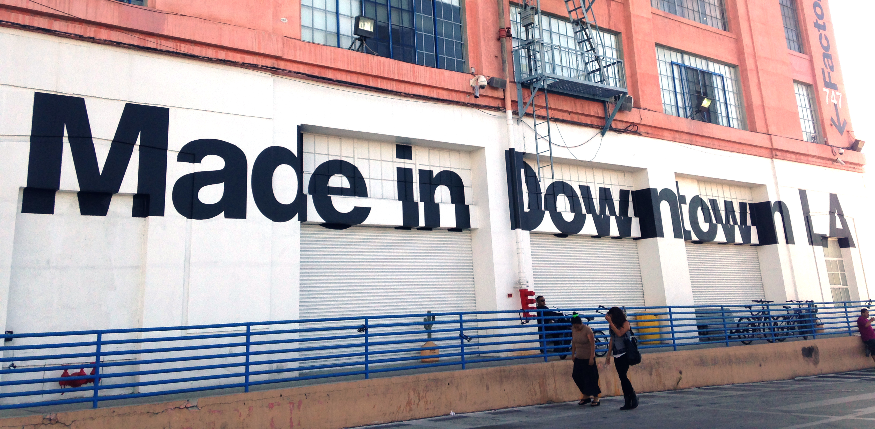 Two people walk past the American apparel factory building and outlet store in Los Angeles, California July 7, 2014. Ousted American Apparel Inc head Dov Charney supported workers in the clothing industry with his stance in favor of immigration rights and determination to keep jobs in the United States, but some employees are not returning the favor. Last month American Apparel's board dismissed Charney. It accused the chairman, president and chief executive of misusing corporate funds and failing to prevent the dissemination of nude photos of a female ex-employee who sued him. Picture taken July 7, 2014. To match Feature AMERICAN-APPAREL-WORKERS/ REUTERS/Lisa Baertlein (UNITED STATES - Tags: BUSINESS EMPLOYMENT SOCIETY CRIME LAW) - RTR3XO82