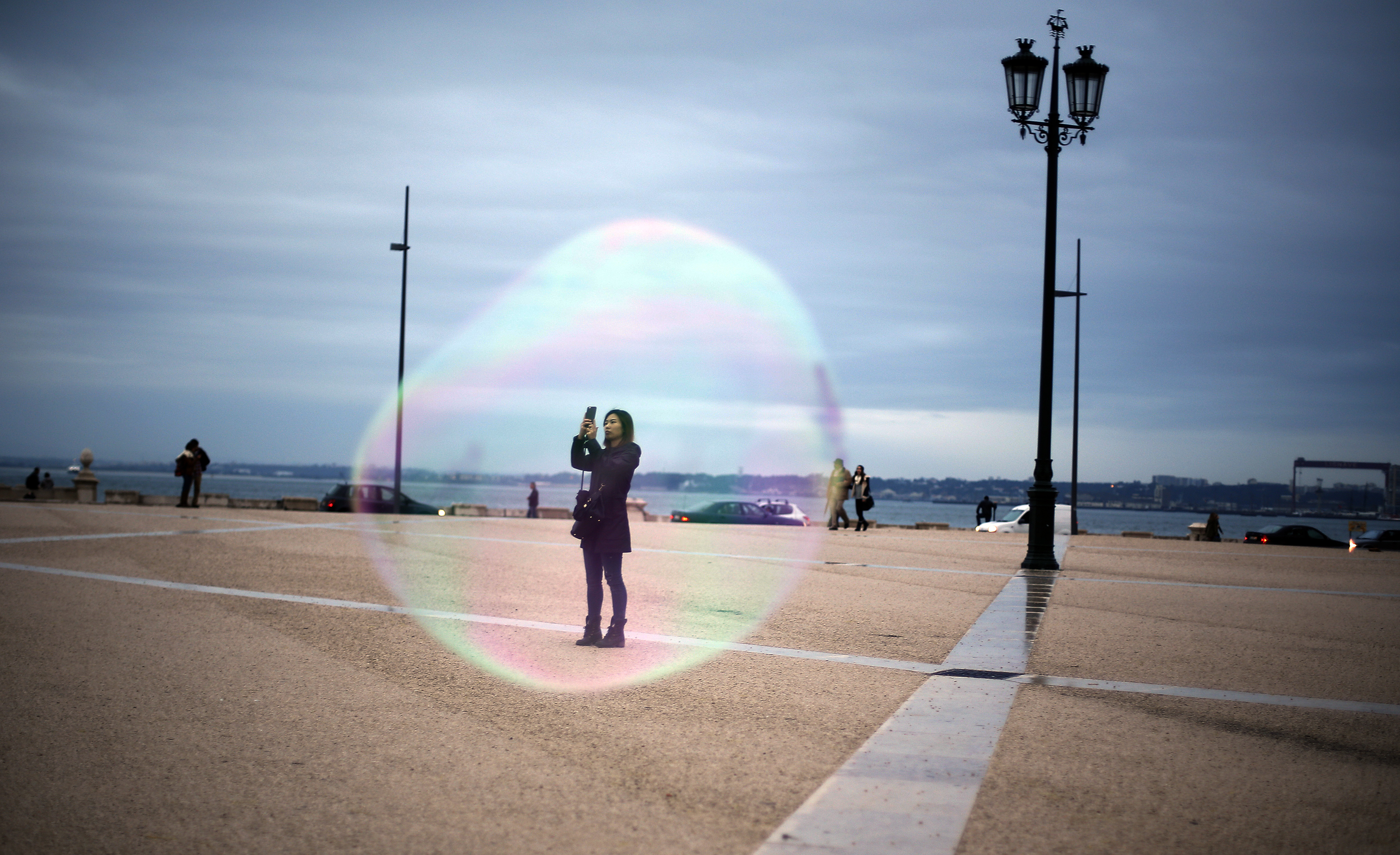 A tourist is seen through a soap bubble as she takes a picture at Comercio square in downtown Lisbon November 18, 2014.  REUTERS/Rafael Marchante (PORTUGAL - Tags: SOCIETY TPX IMAGES OF THE DAY) - RTR4EN2S