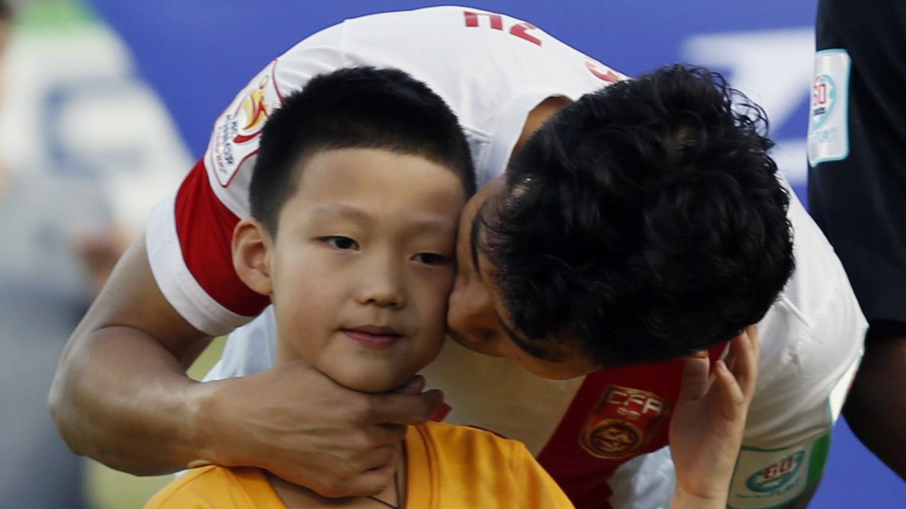 China's captain Zheng Zhi kisses a mascot as the team line up before the start of their Asian Cup Group B soccer match against North Korea at the Canberra stadium in Canberra January 18, 2015.