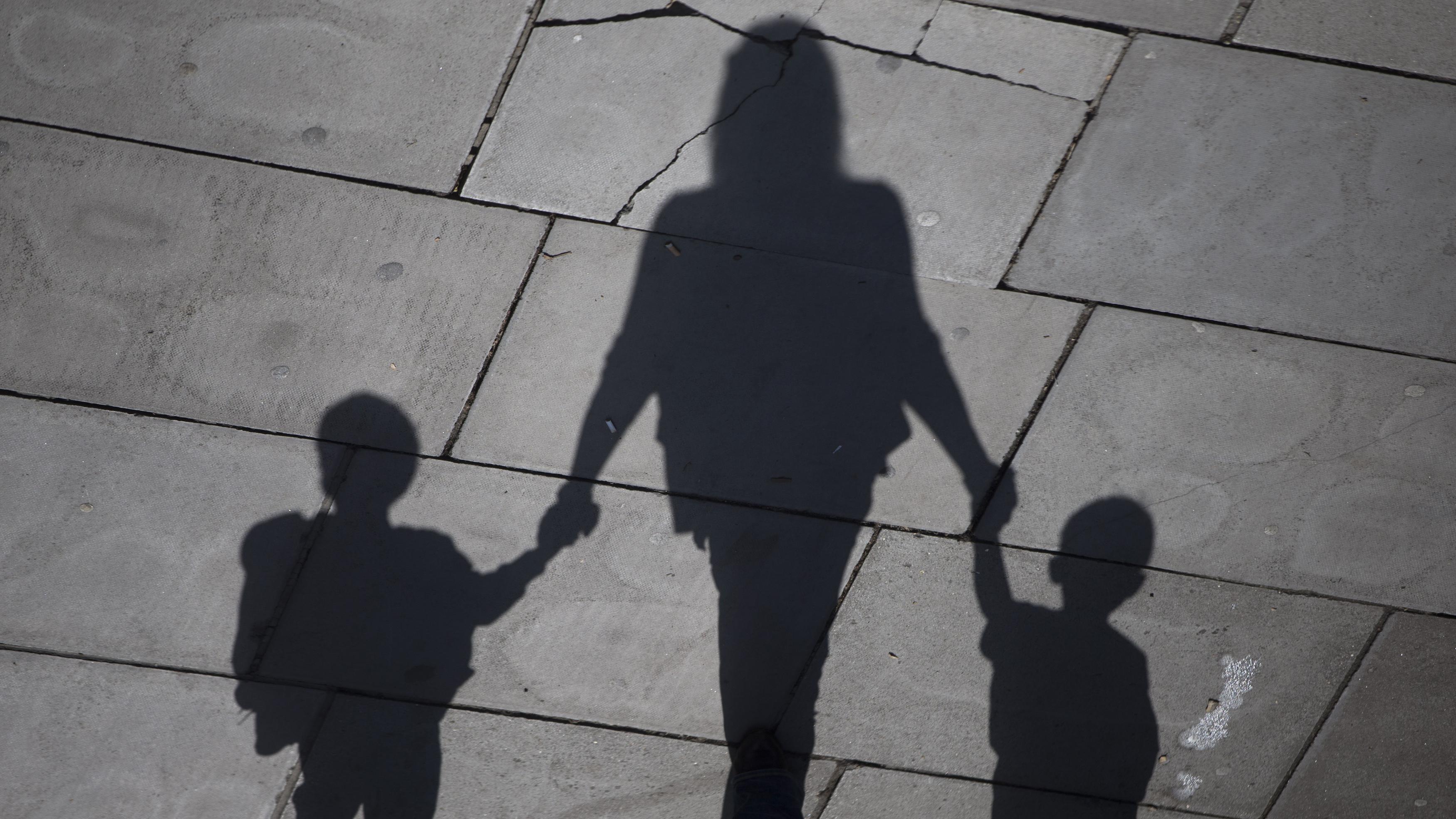 A woman and children cast their shadows