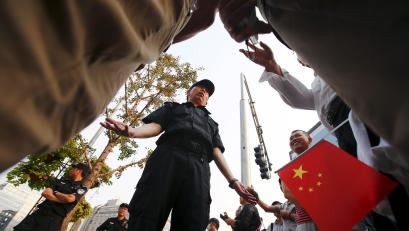A man holding a Chinese flag and bystanders talk to a policeman blocking the area around the China Securities Regulatory Commission, during a protest against the Fanya Mental Exchange in Beijing September 21, 2015. Hundreds of investors gathered outside the headquarters of China's securities watchdog on Monday to protest against a metals exchange in a southwest province they accuse of defrauding them of billions of yuan.