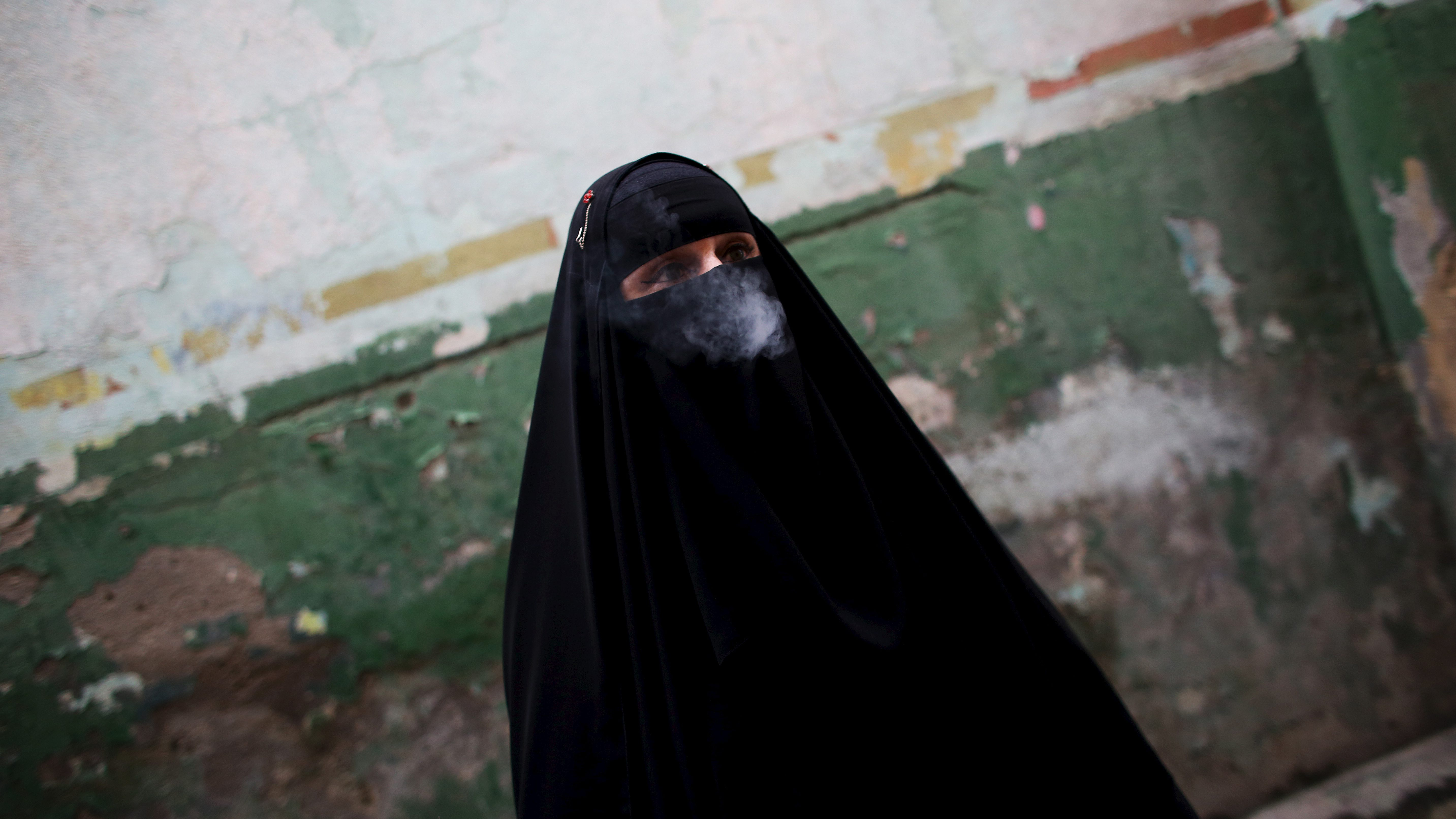 """Gisele Marie, a Muslim woman and professional heavy metal musician, smokes a cigarette before a fund raising concert for Syrian refugges in Brazil, in Rio de Janeiro November 8, 2015. Based in Sao Paulo, Marie, 42, is the granddaughter of German Catholics, and converted to Islam several months after her father passed away in 2009. Marie, who wears the Burka, has been fronting her brothers' heavy metal band """"Spectrus"""" since 2012. """"People do not expect to see a Muslim woman who uses a burqa, practices the religion properly and is a professional guitarist who plays in a heavy metal band, so many people are shocked by it. But other people are curious and find it interesting, and others think that it is cool, but definitely, many people are shocked,"""" said Marie. Picture taken November 8, 2015. REUTERS/Nacho Doce  - RTS66WL"""