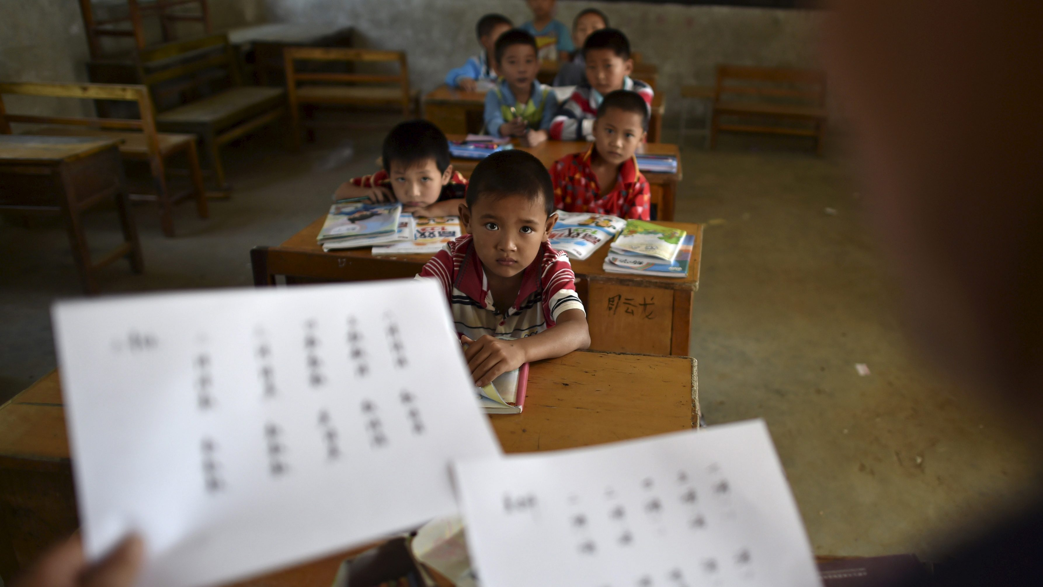 """Students look at their teacher holding papers of the new curriculum at a classroom of Dalu primary school in Gucheng township of Hefei, Anhui province, China, September 8, 2015. The school, opened in 2006 and has never acquired a legal license, may face a shutdown order from the government. There are currently over 160 students in the school, mostly """"leftover children"""", whose parents left their hometown to earn a living, local media reported. Picture taken September 8, 2015."""