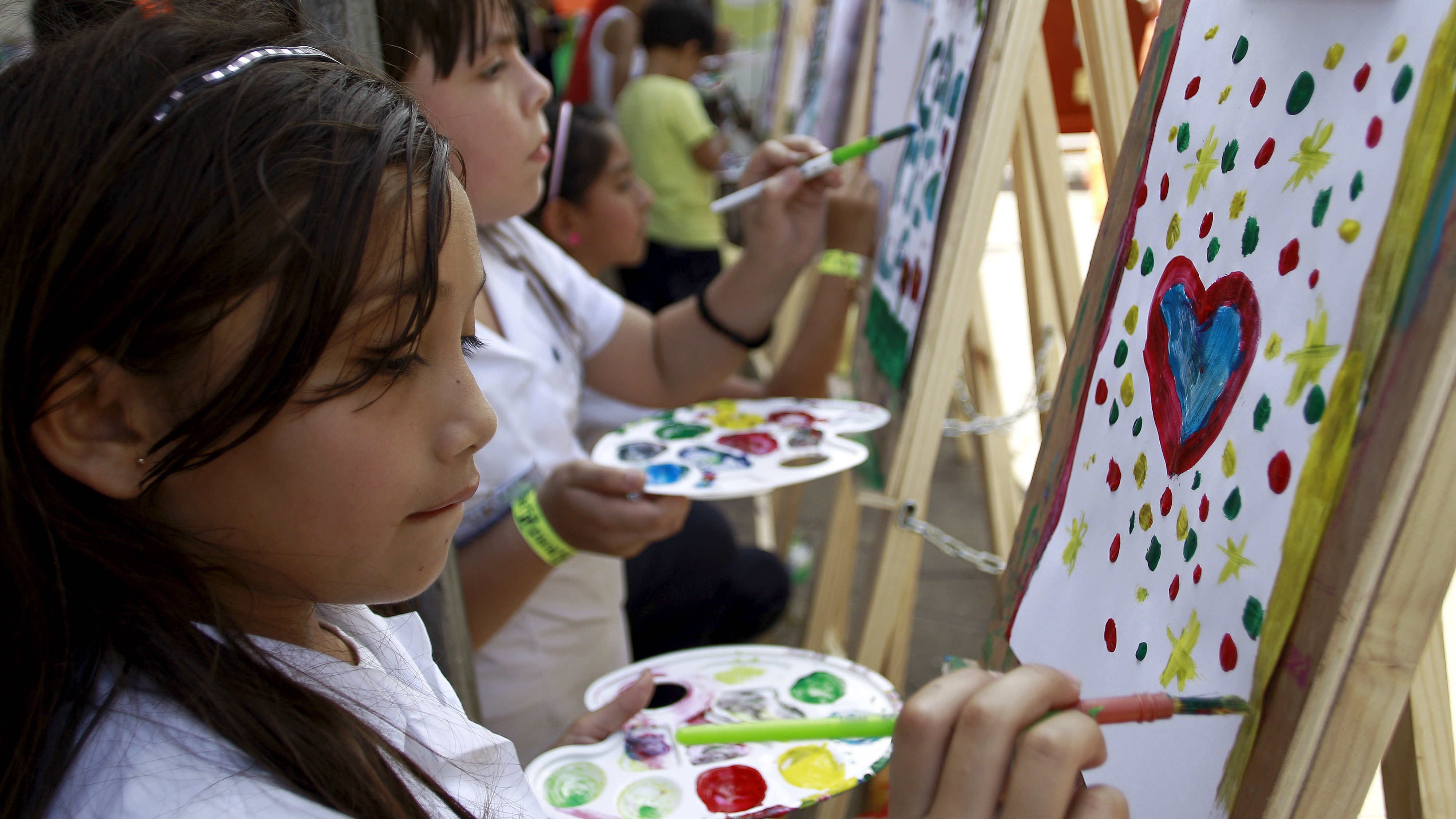 Costa Ricans girls paint during celebrations of National Children's Day in San Jose