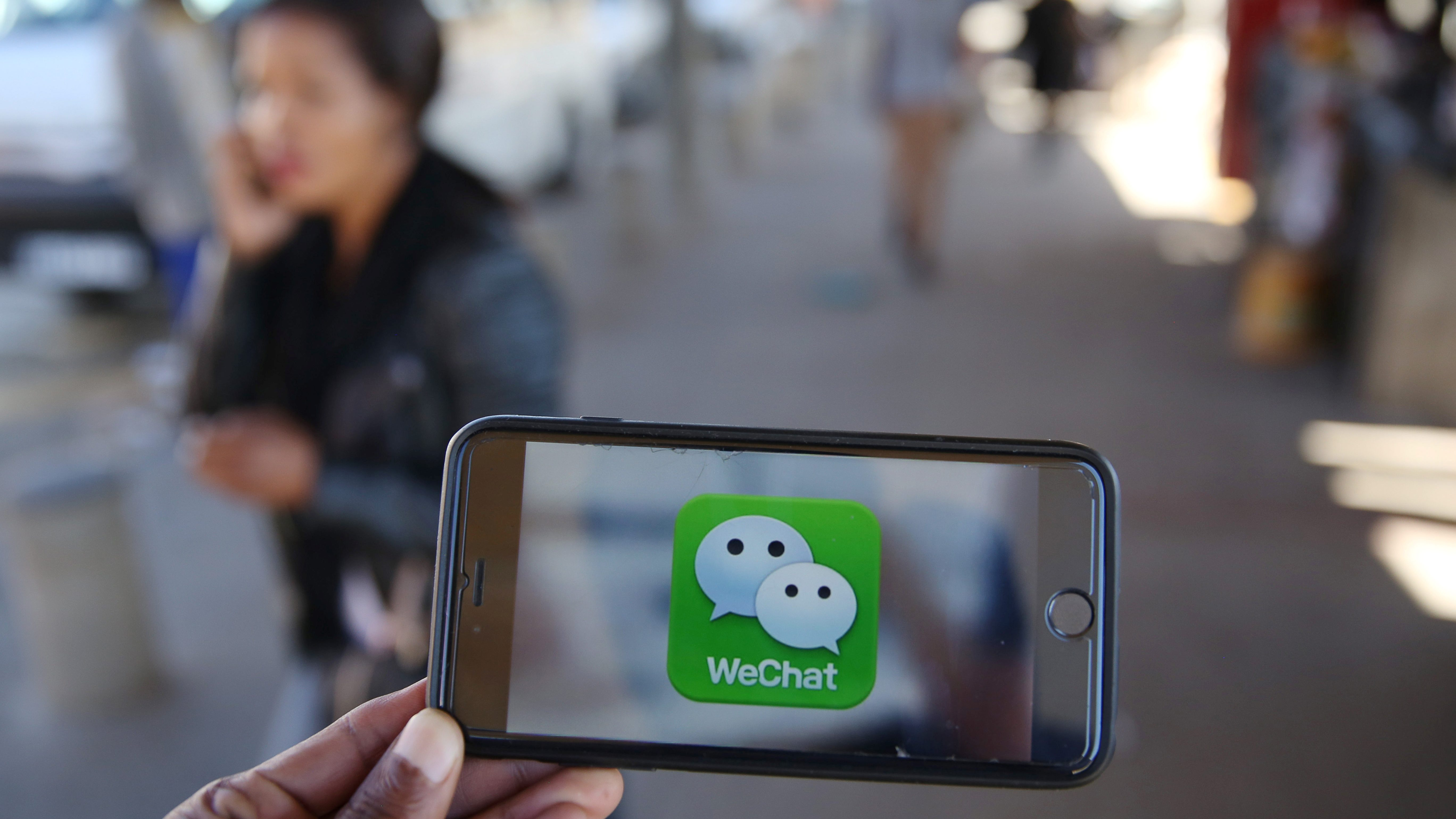 A WeChat logo is displayed on a mobile phone as a woman walks past as she talks on her mobile phone at a taxi rank in this picture illustration