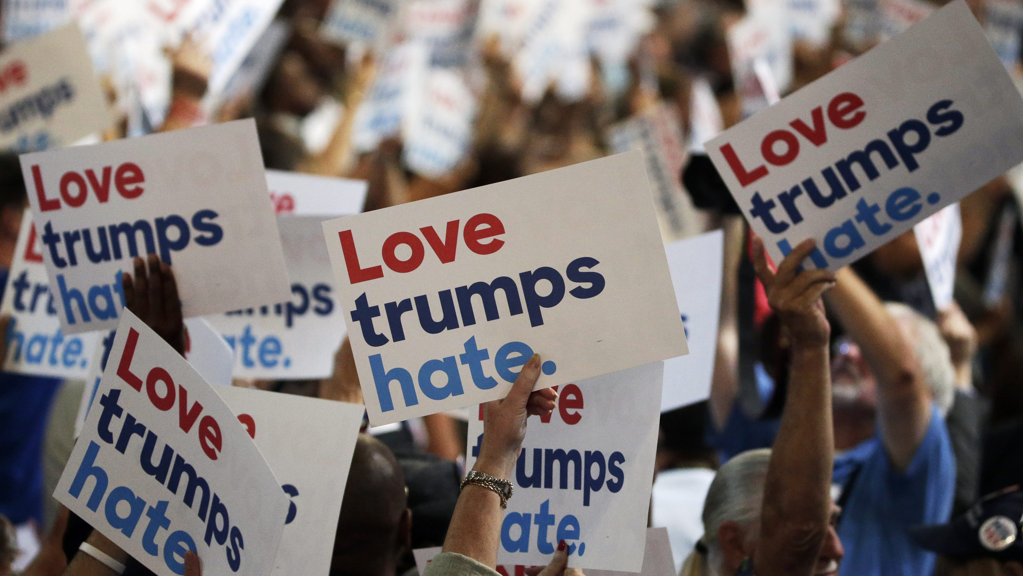 People hold anti-Donald Trump signs