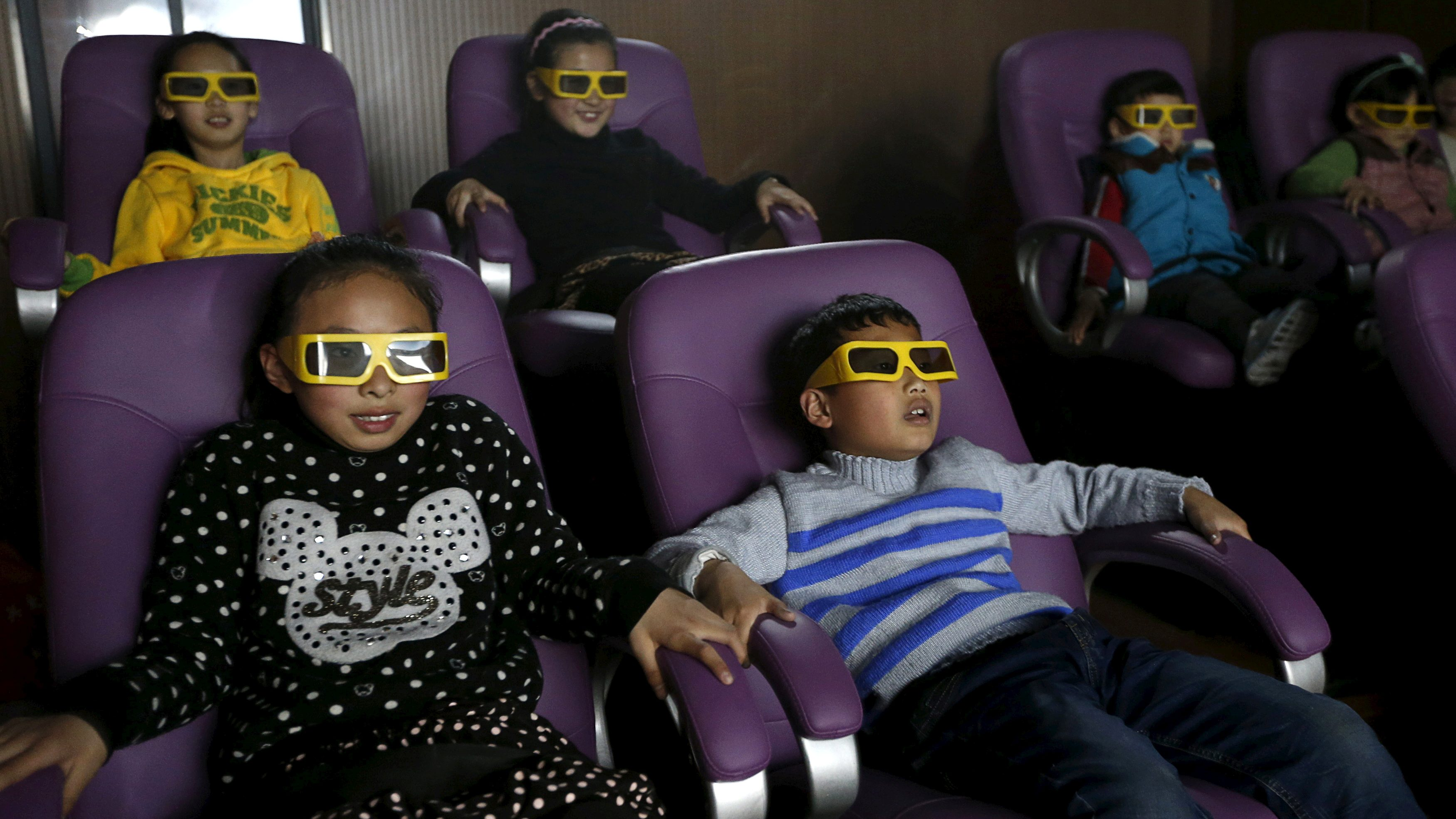Children watch a 3D war movie at a community theatre in Hefei, Anhui province, March 29, 2015.