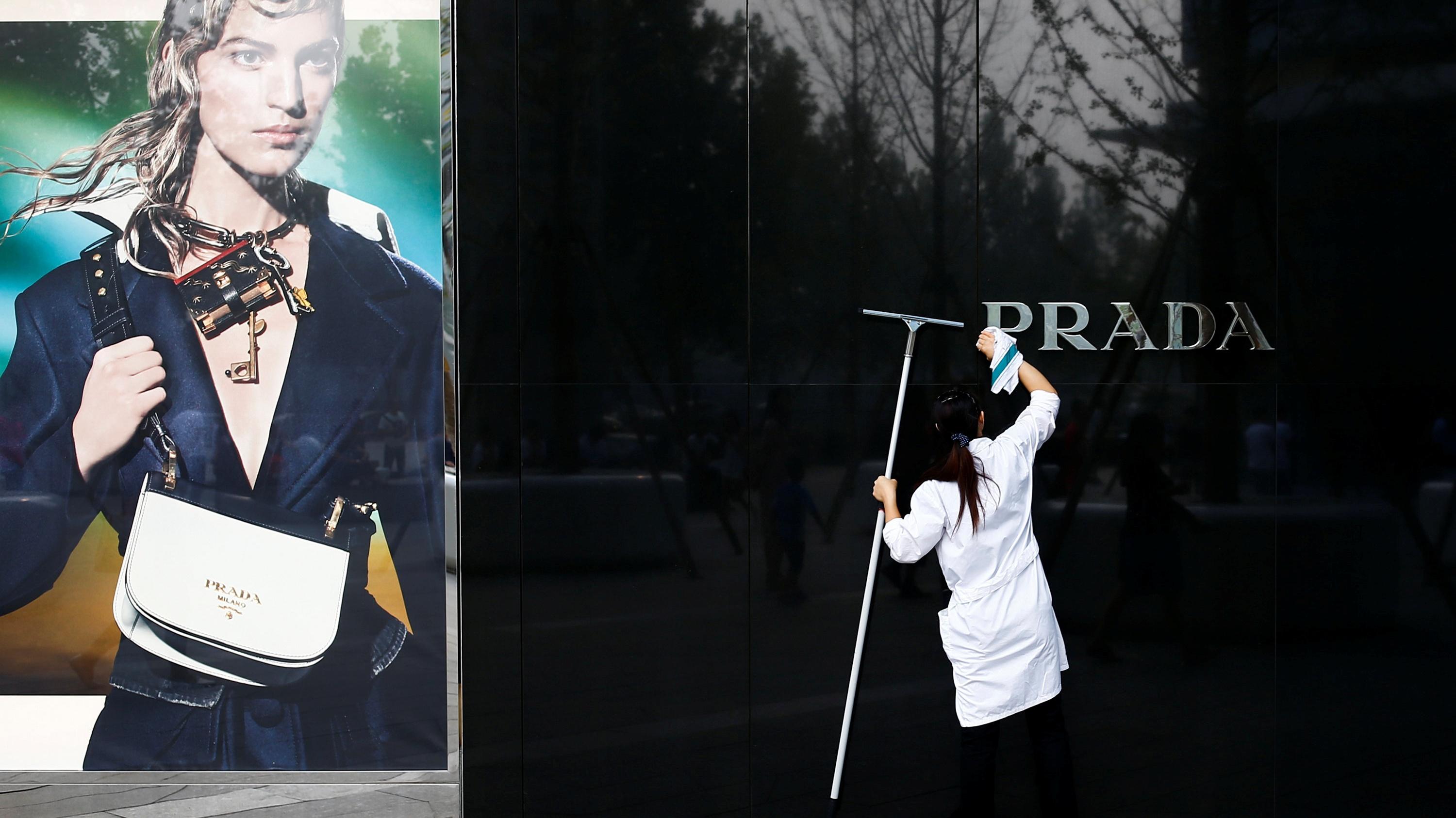 A woman cleans the brand logo at a Prada fashion boutique in Beijing, China, September 16, 2016. REUTERS/Thomas Peter