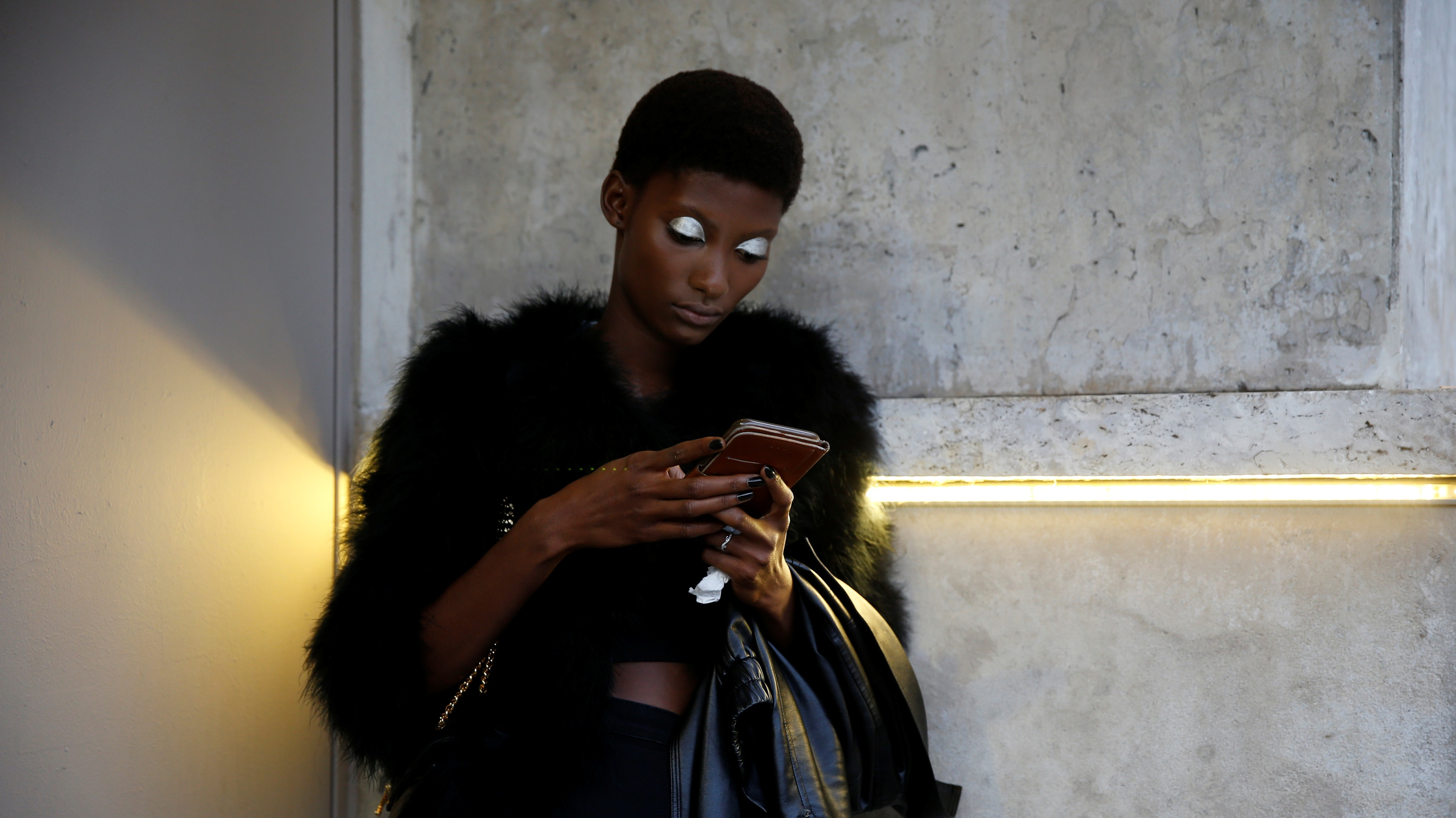 A model uses her mobile phone as she waits before the German designer Lutz Huelle Spring/Summer 2017 women's ready-to-wear collection during Fashion Week in Paris, France September 30, 2016. REUTERS/Gonzalo Fuentes