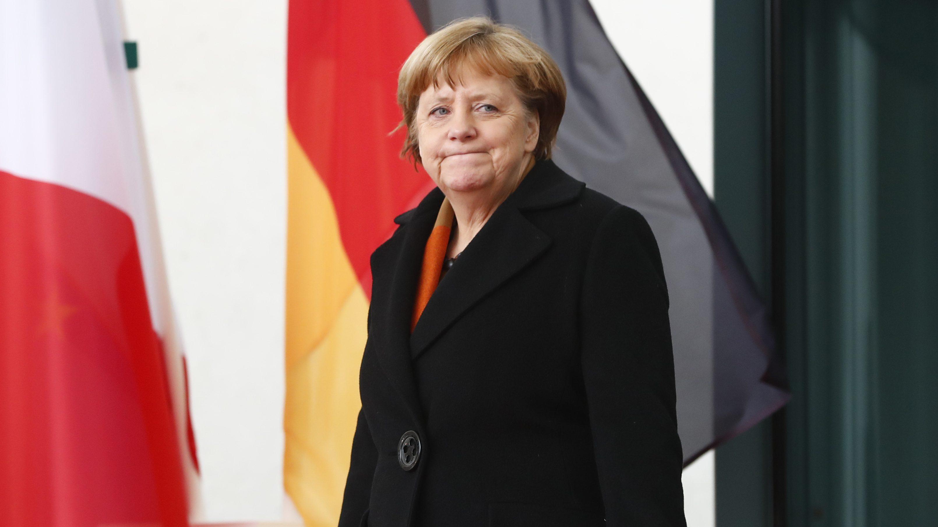 German Chancellor Angela Merkel  in front of flags