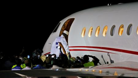 Former Gambian president Yahya Jammeh boards a private jet before departing Banjul airport.